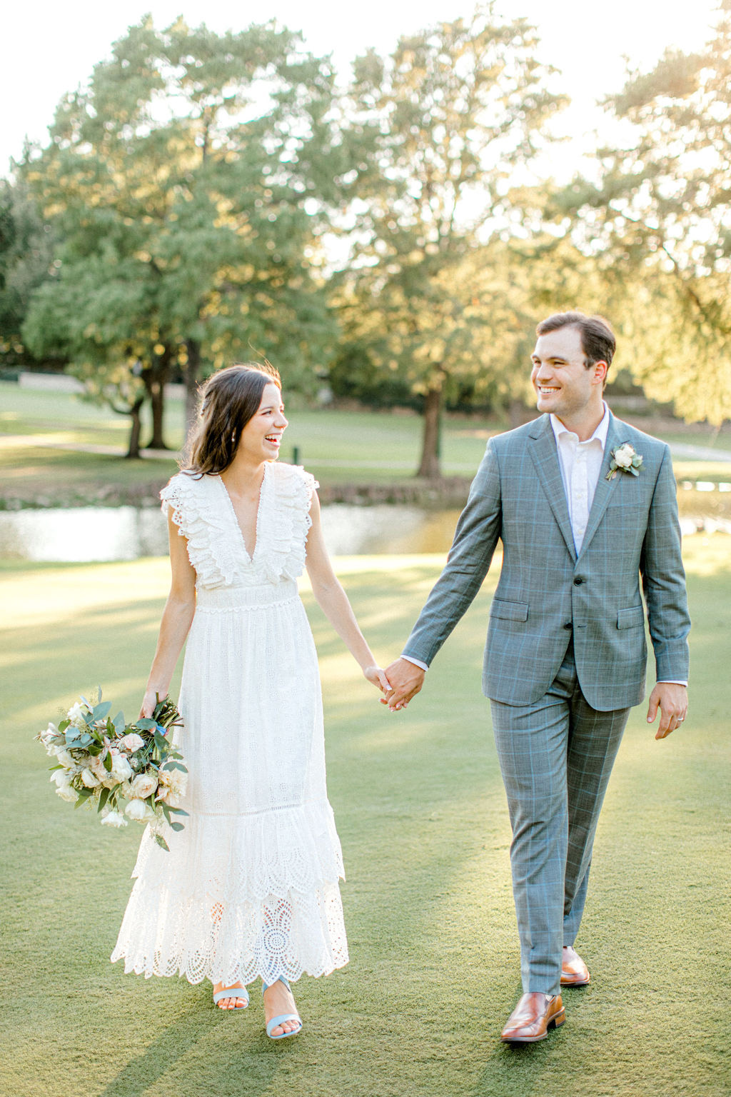 bride and groom holding hands smiling walking outside