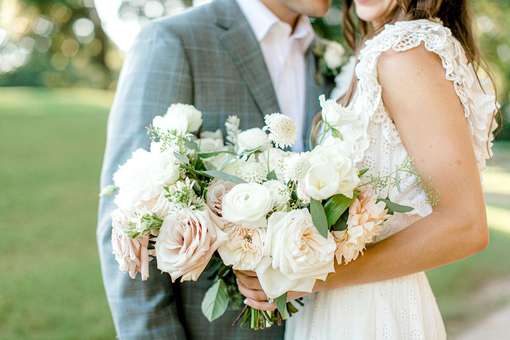 bride holding blush and white floral bouquet with groom