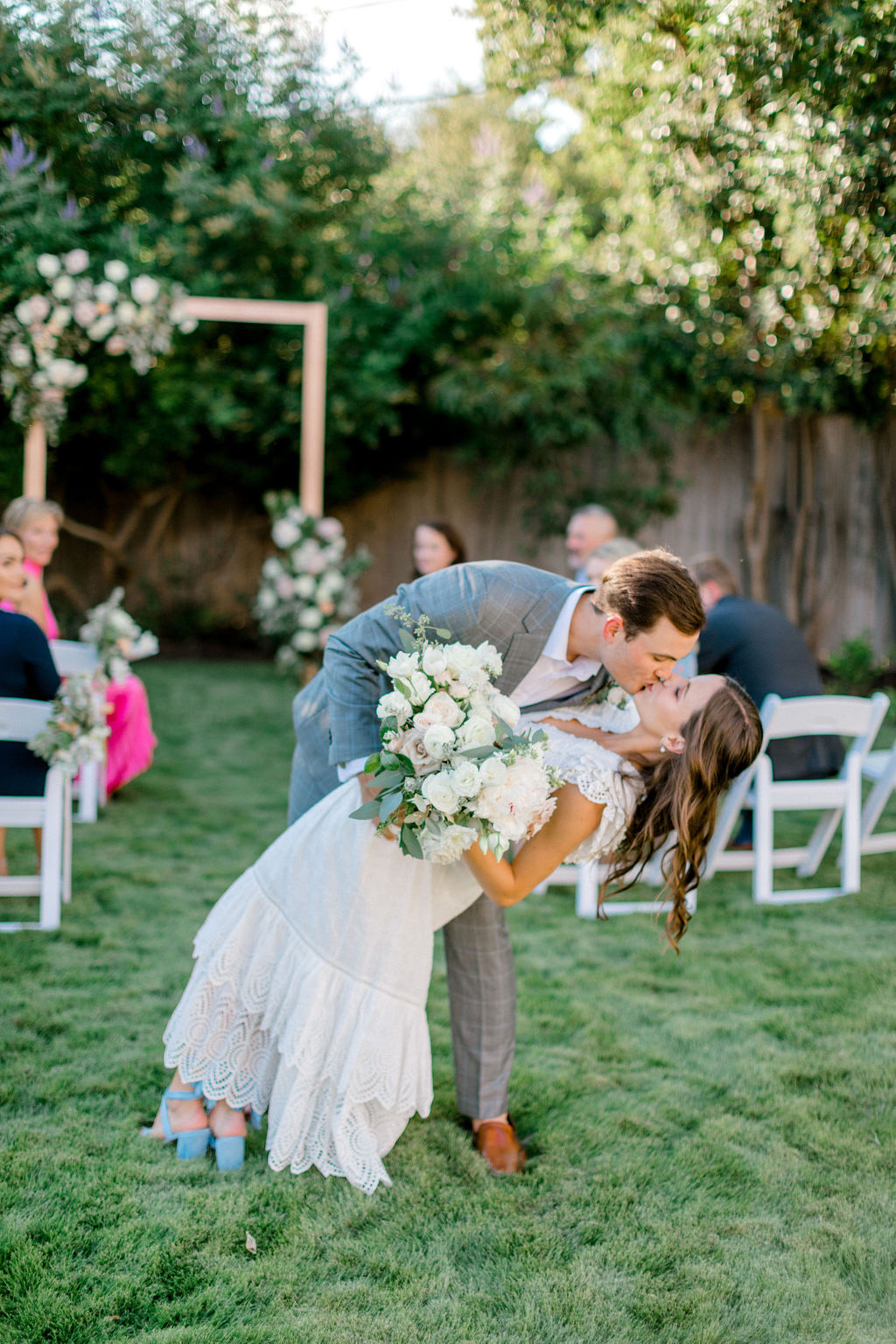 groom dips bride for a kiss after wedding ceremony