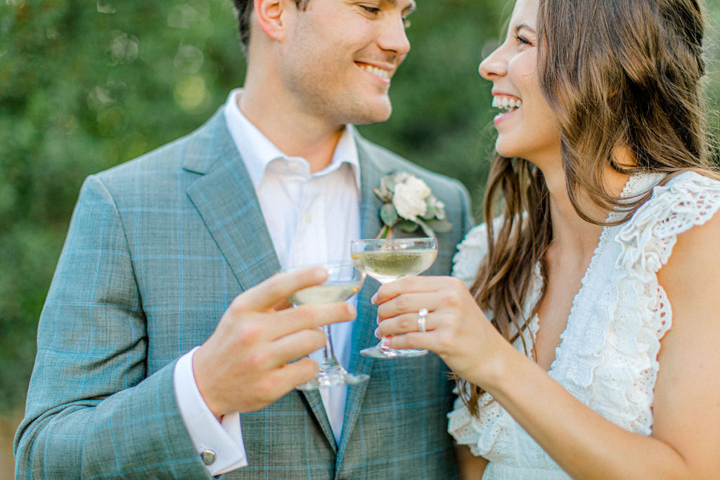 bride and groom smiling with champagne