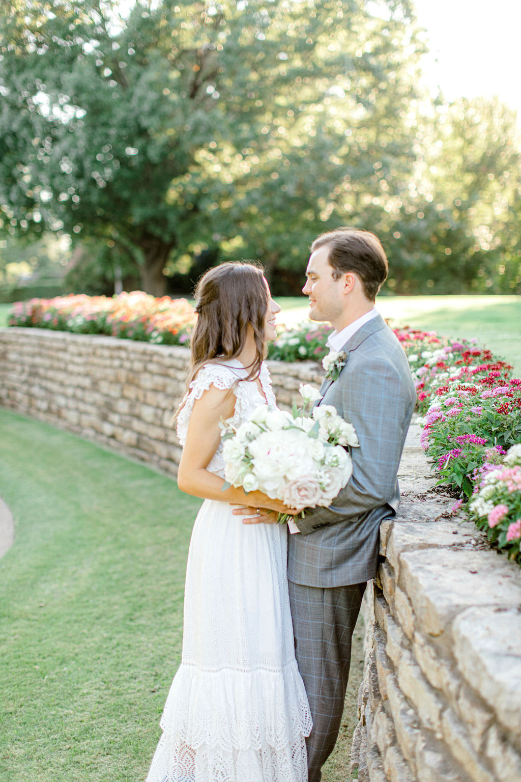 groom leaning on stone wall with bride smiling at him