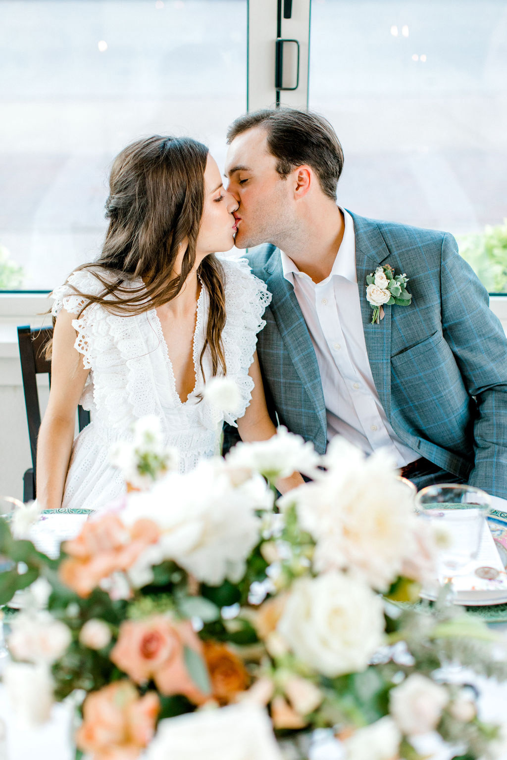 bride and groom share a kiss at reception table