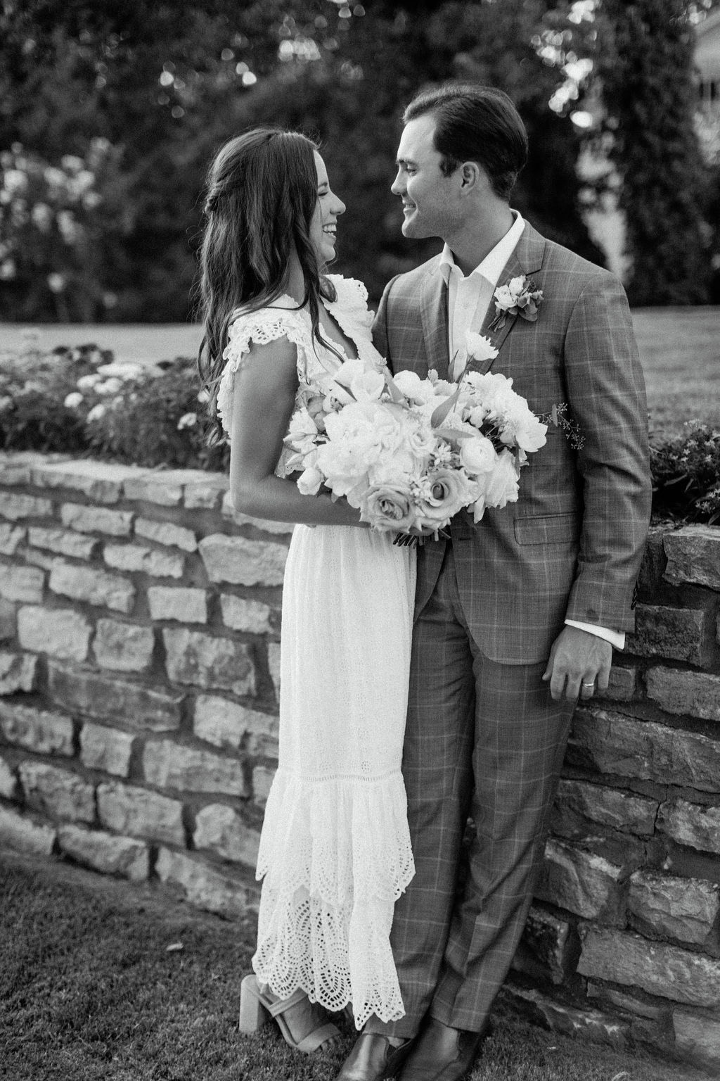 bride and groom leaning on stone wall outside smiling at each other