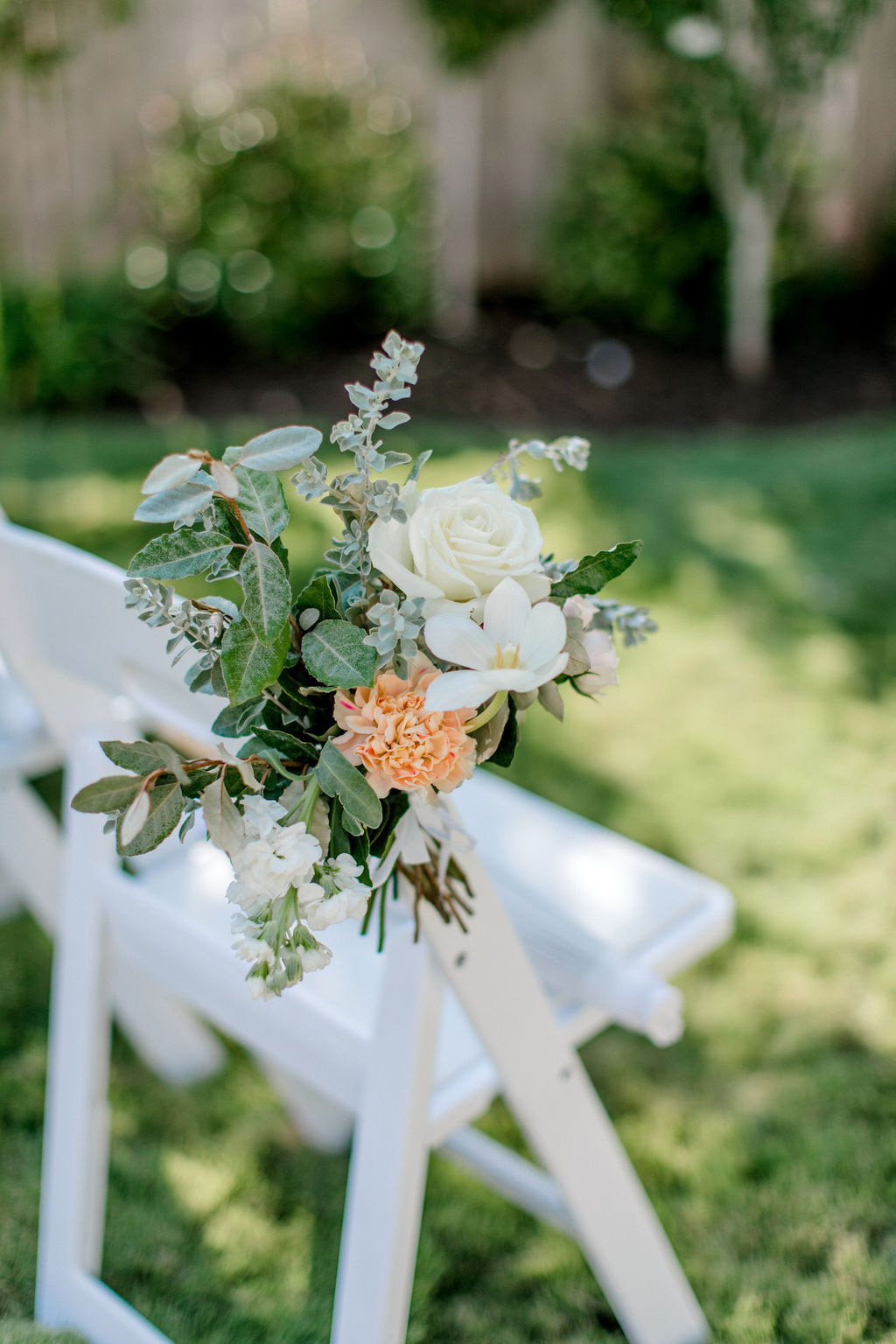 small floral accents on white wedding ceremony seating