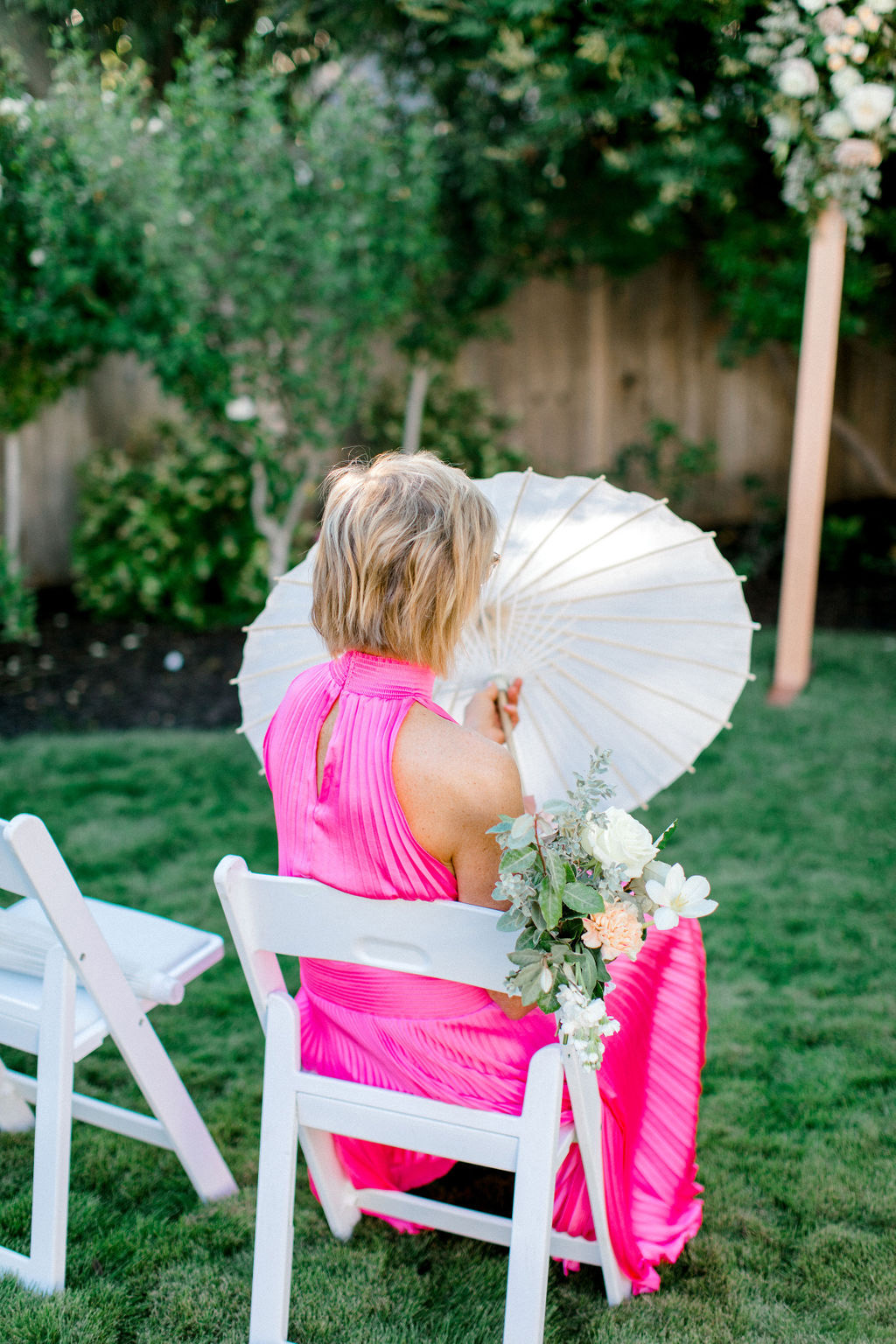 guess in bright pink dress holding white parasol