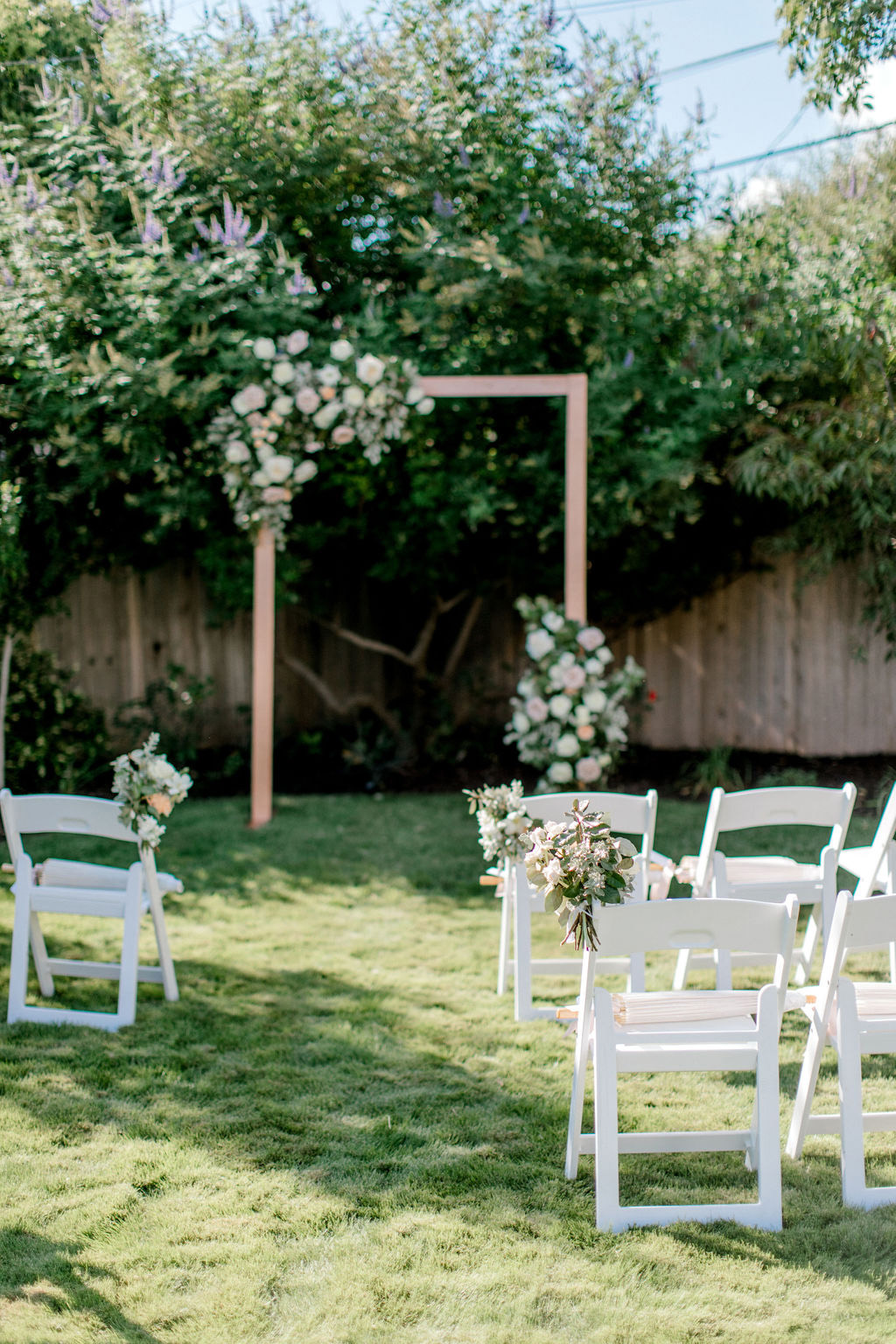wooden ceremony arch with floral decor in front of white chair seating area