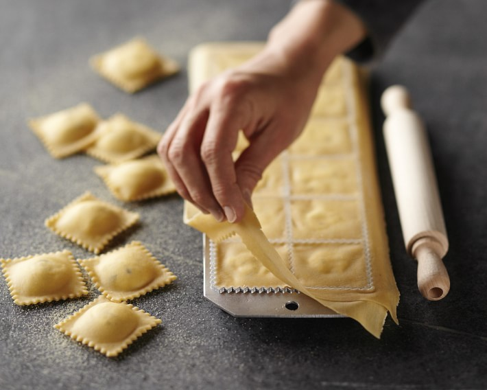 person using ravioli mold with roller