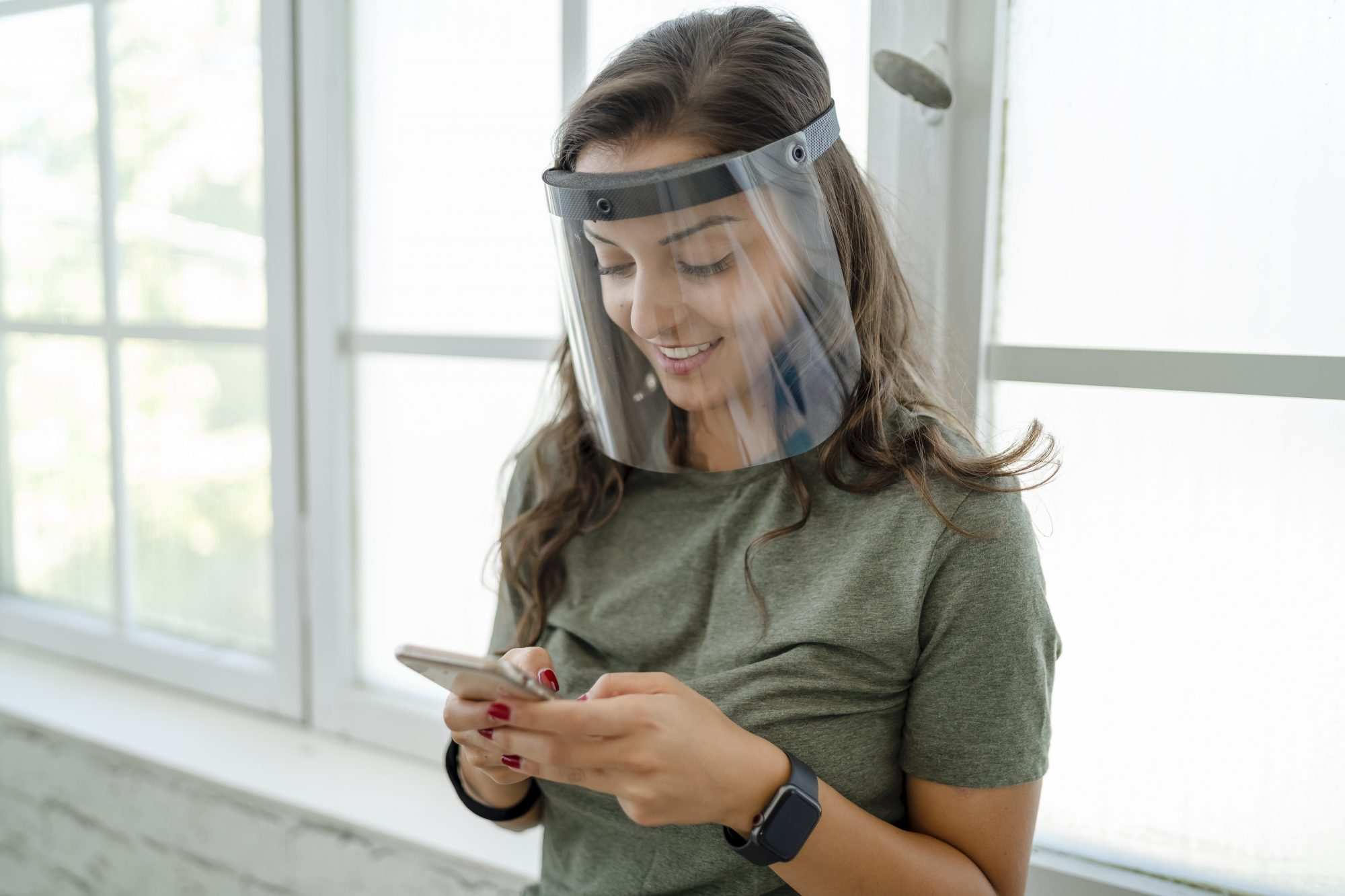 woman wearing face shield texting on phone