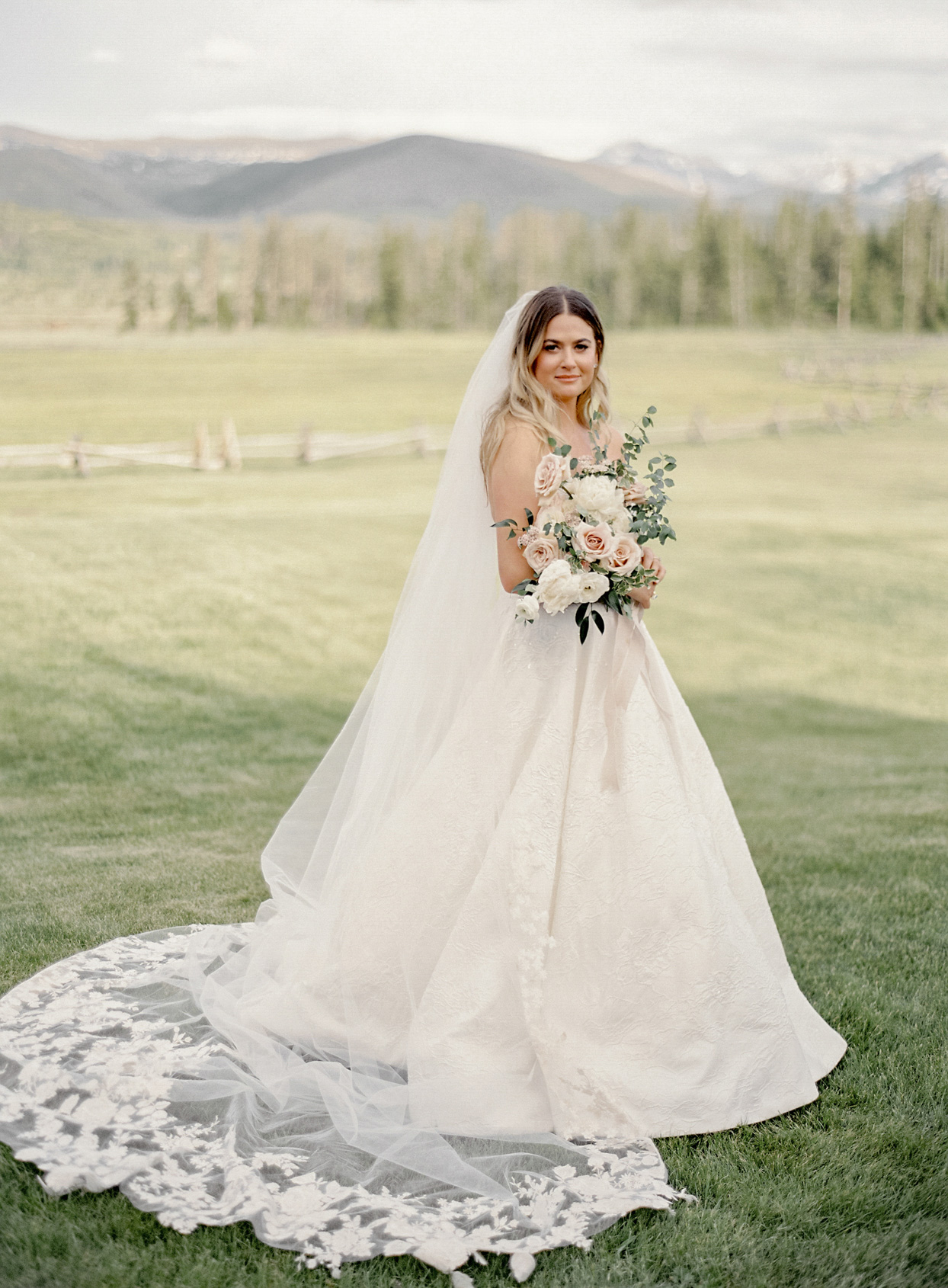bride in white dress standing in field with mountain backdrop