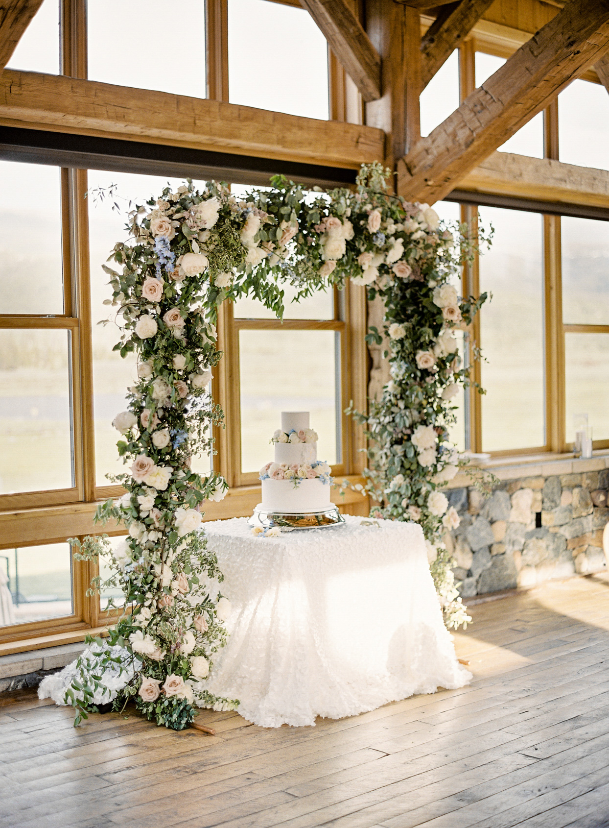wedding cake on white table under floral arch