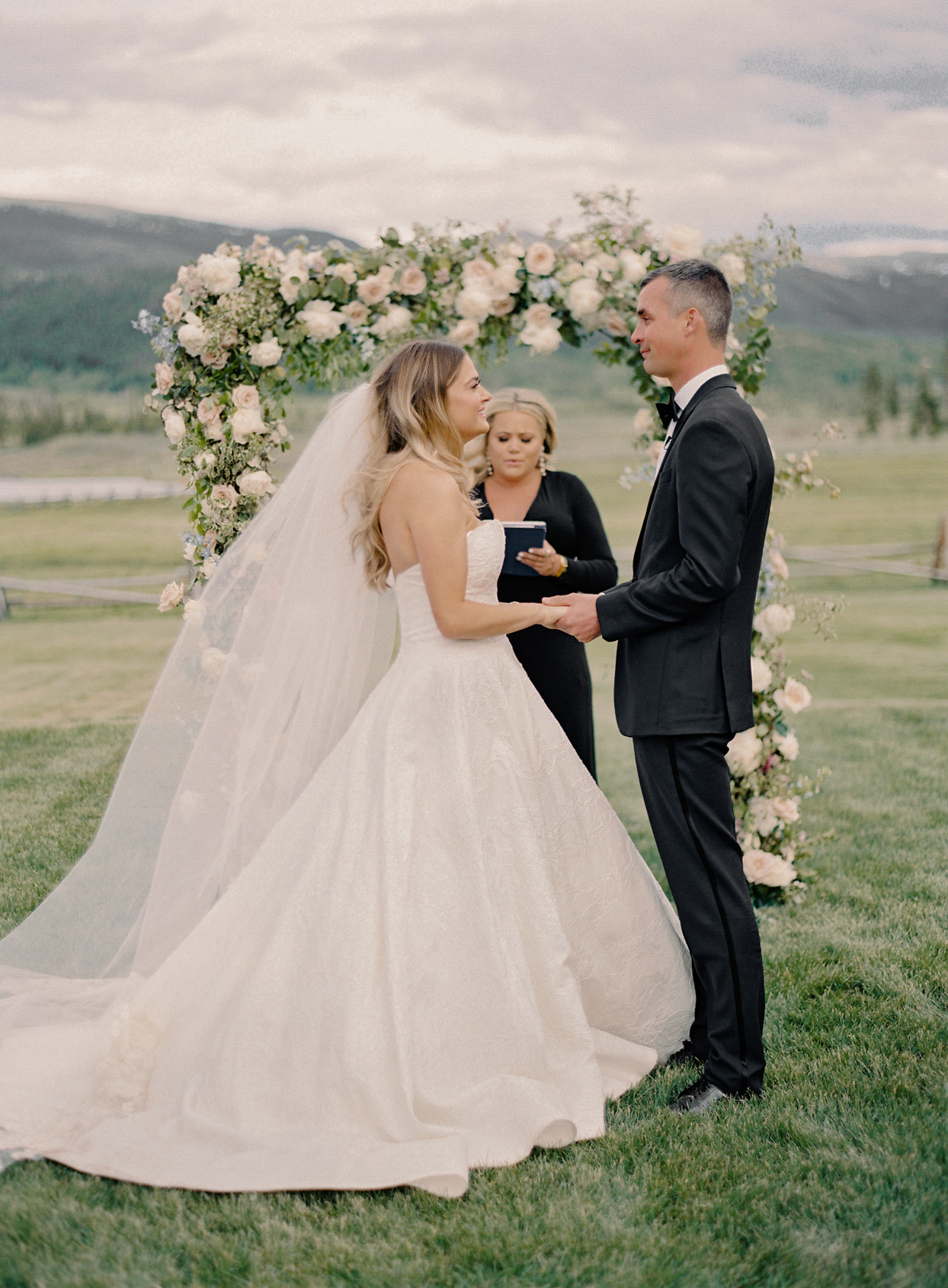 wedding couple holding hands during outdoor ceremony
