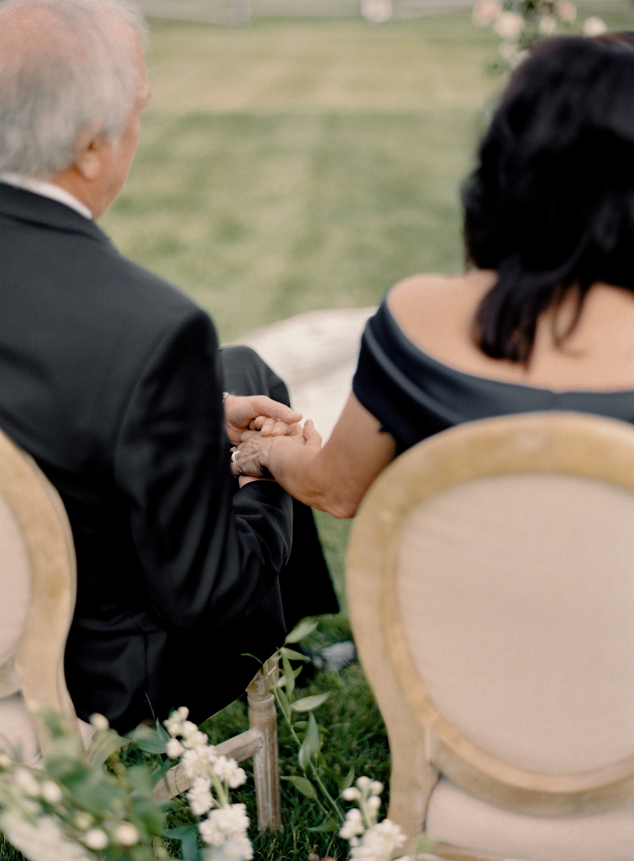 parents holding hands white sitting during wedding ceremony