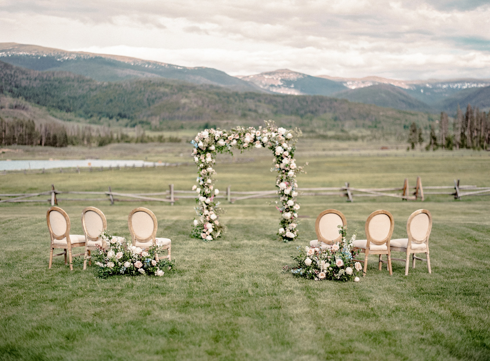 small wedding ceremony setting with floral arch against mountain backdrop