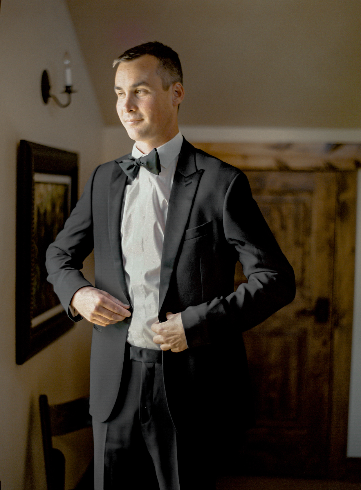 groom putting on black suit jacket with bowtie