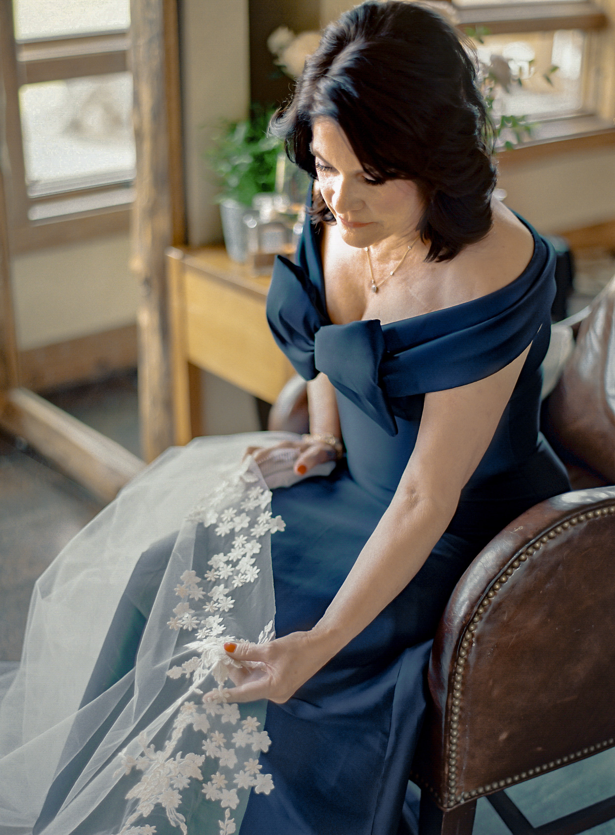 mother of the bride in deep blue dress holding lace veil
