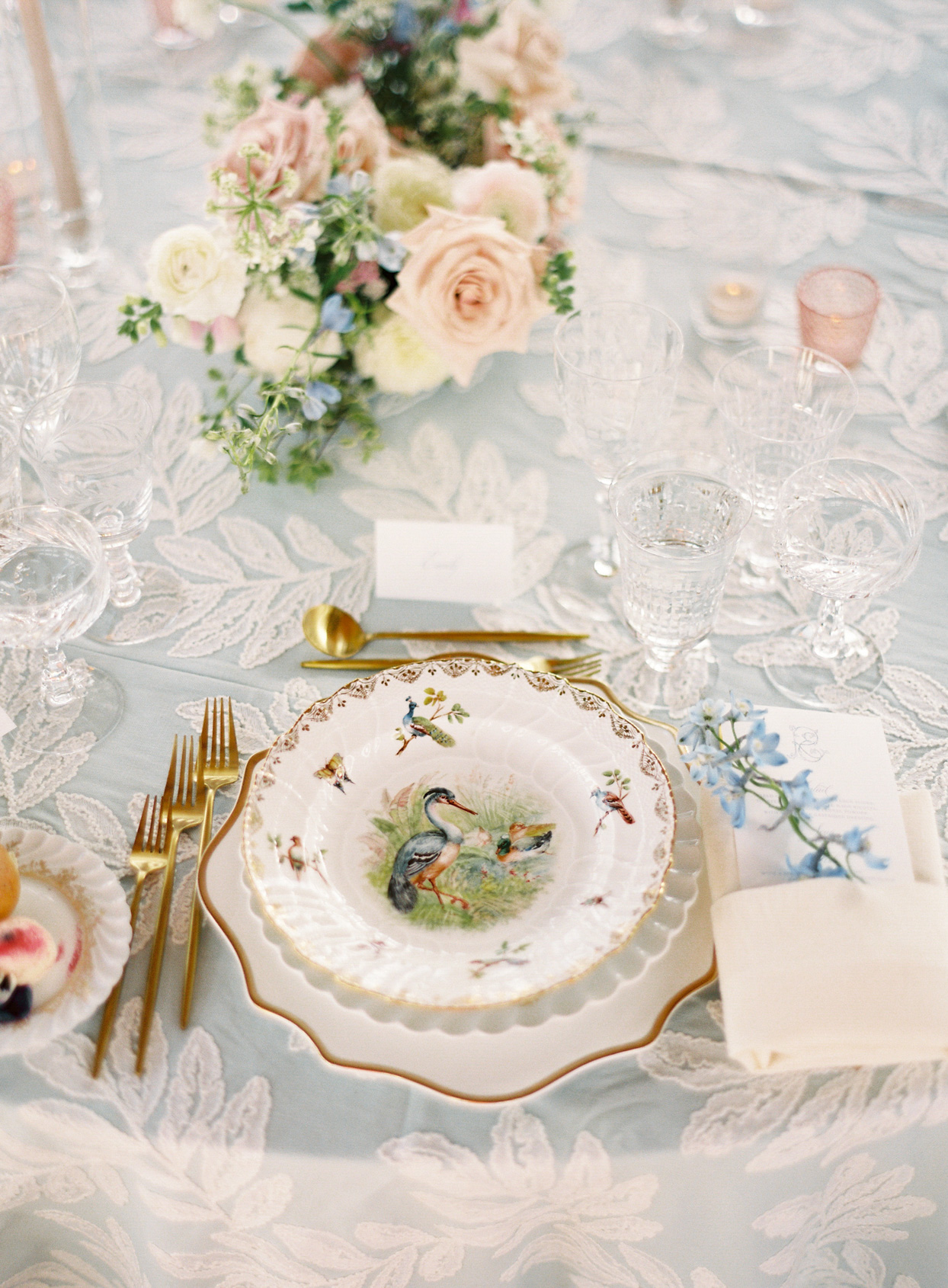 ornate place setting with bird design and golden utensils