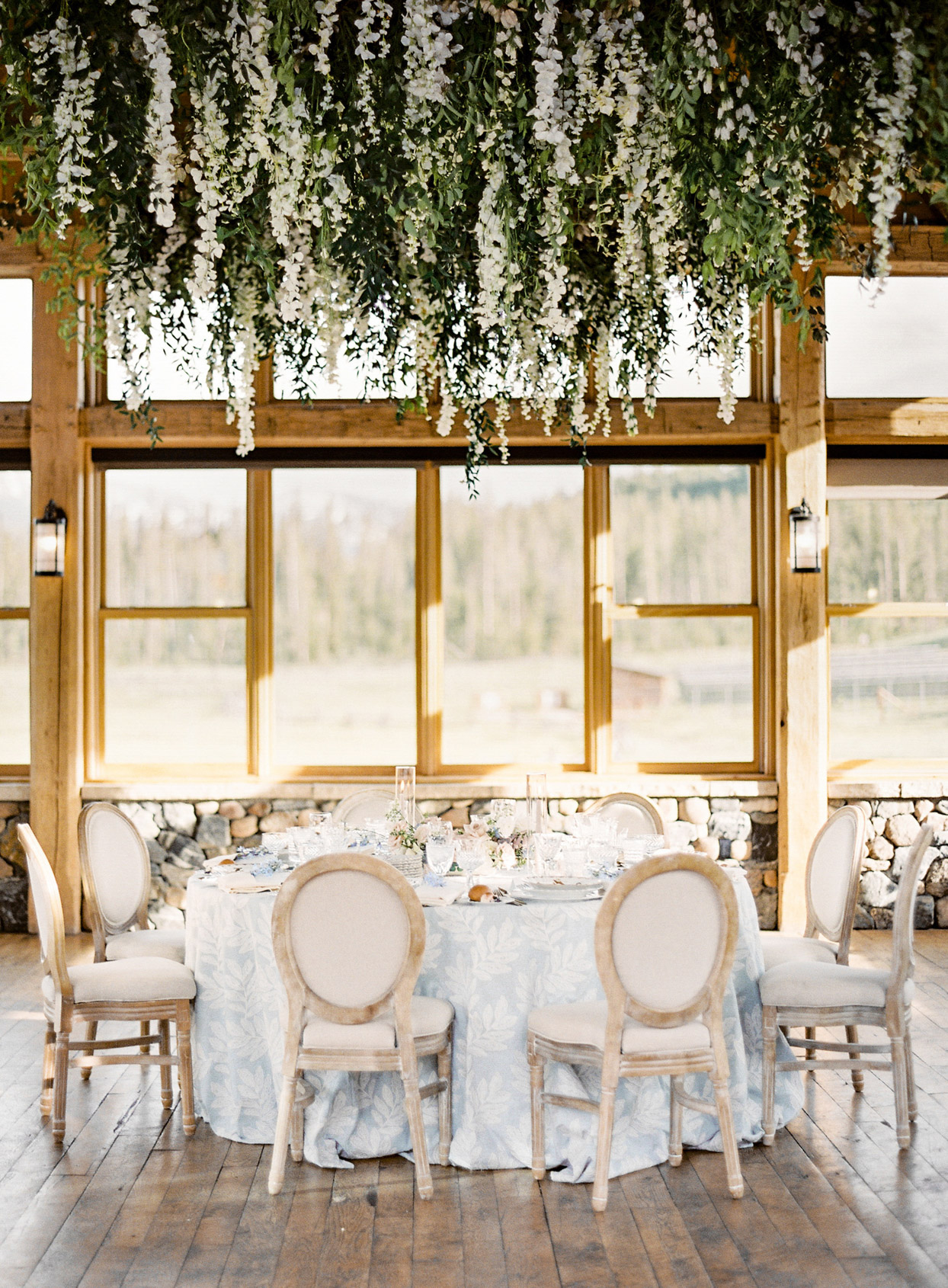 indoor wedding reception tables with large windows and hanging greenery