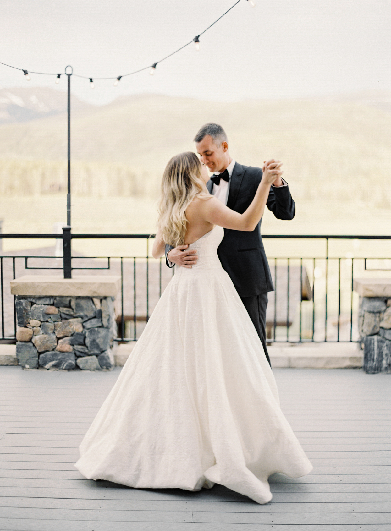 wedding first dance on deck with mountain backdrop
