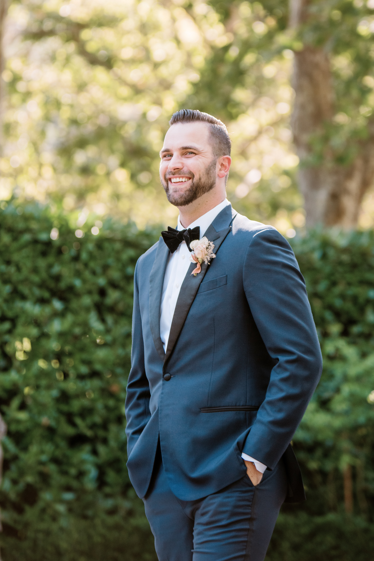 groom in blue suit with pink boutonniere