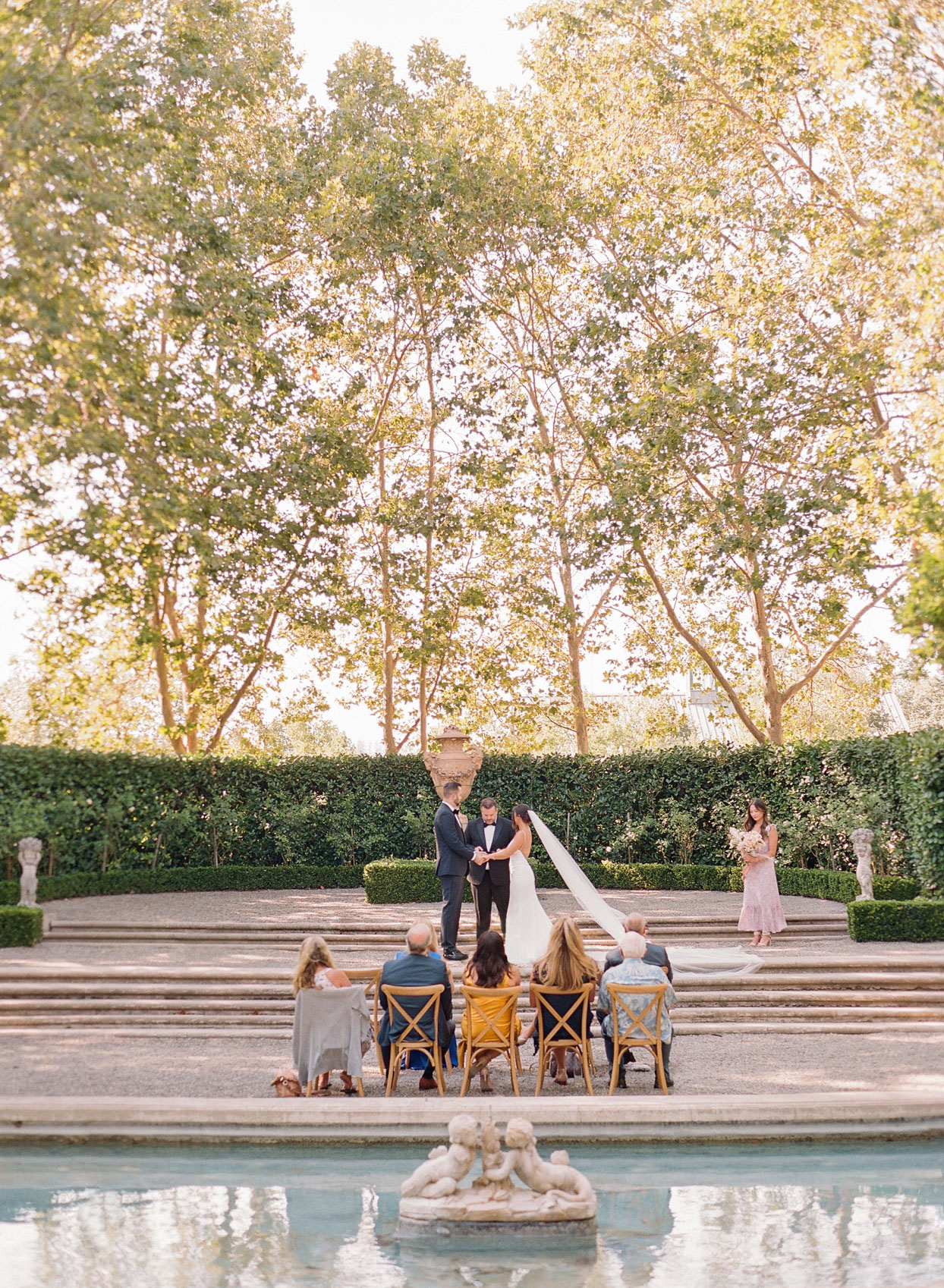 wedding ceremony outdoor garden with water feature and guests in distanced chairs