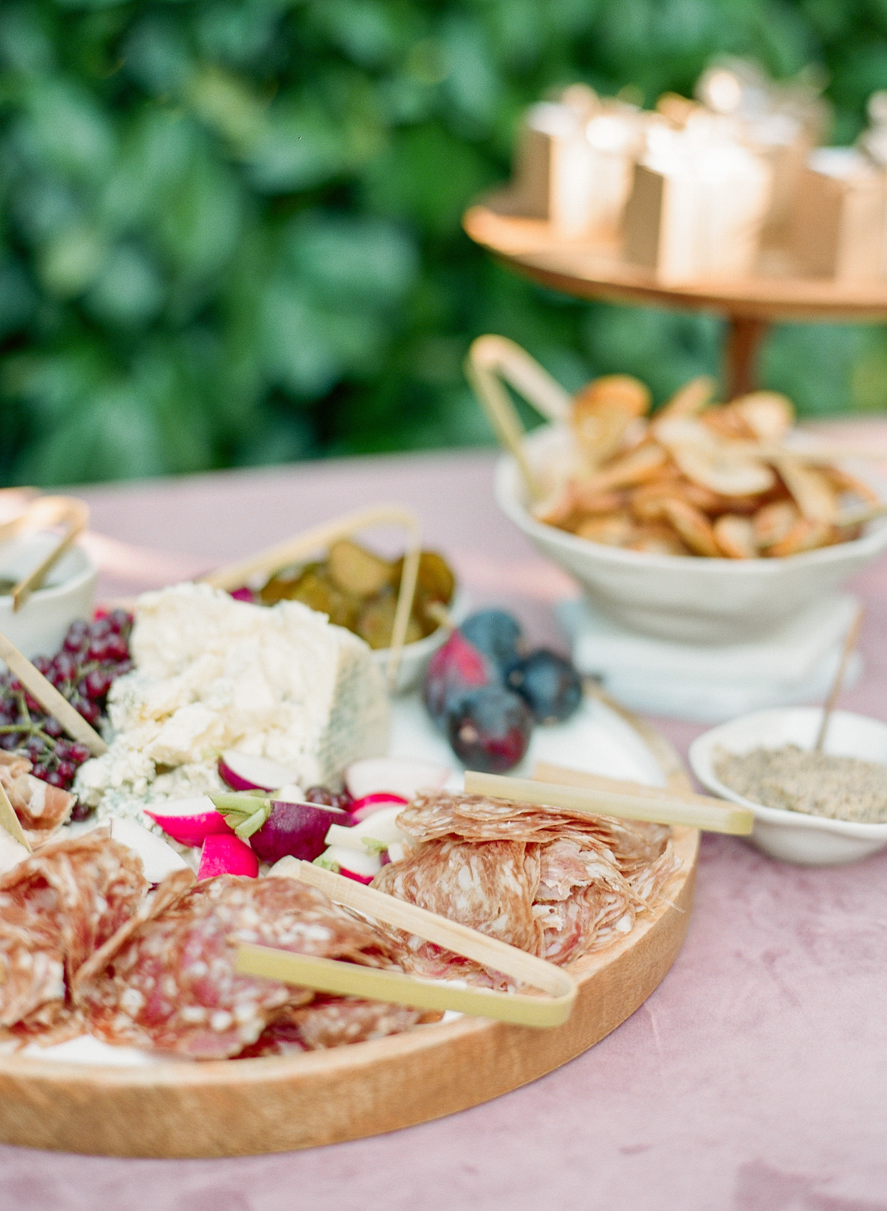 charcuterie board on burgundy tablecloth at wedding