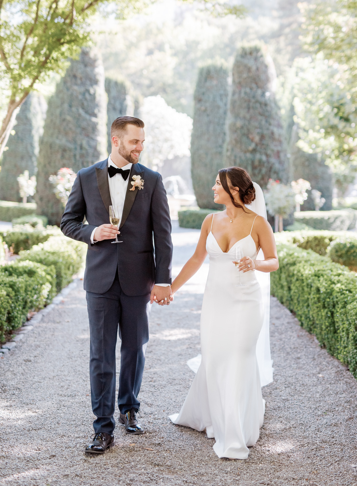 couple holding hands and champagne glasses on garden path