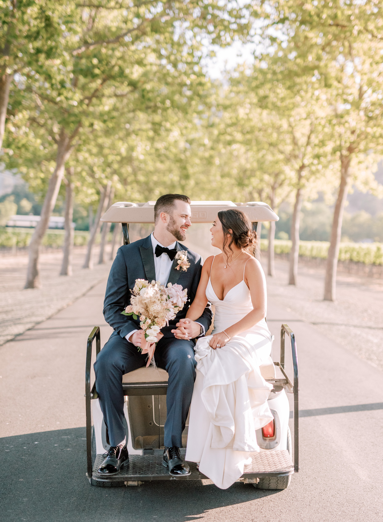 couple sitting on back of golf cart in vineyard path