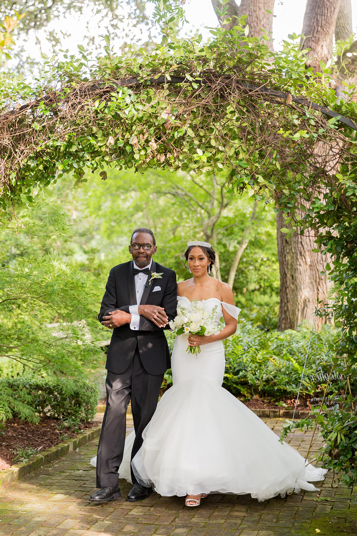 bride with father walking under greenery arch