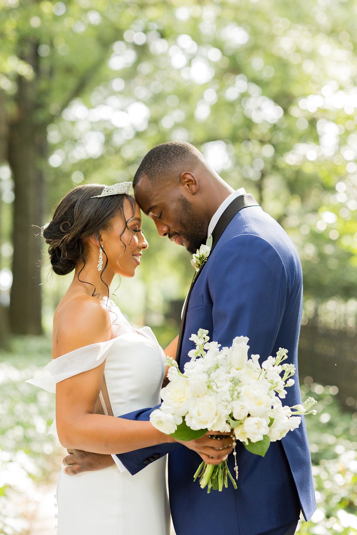 bride and groom hold each other with their heads against one another