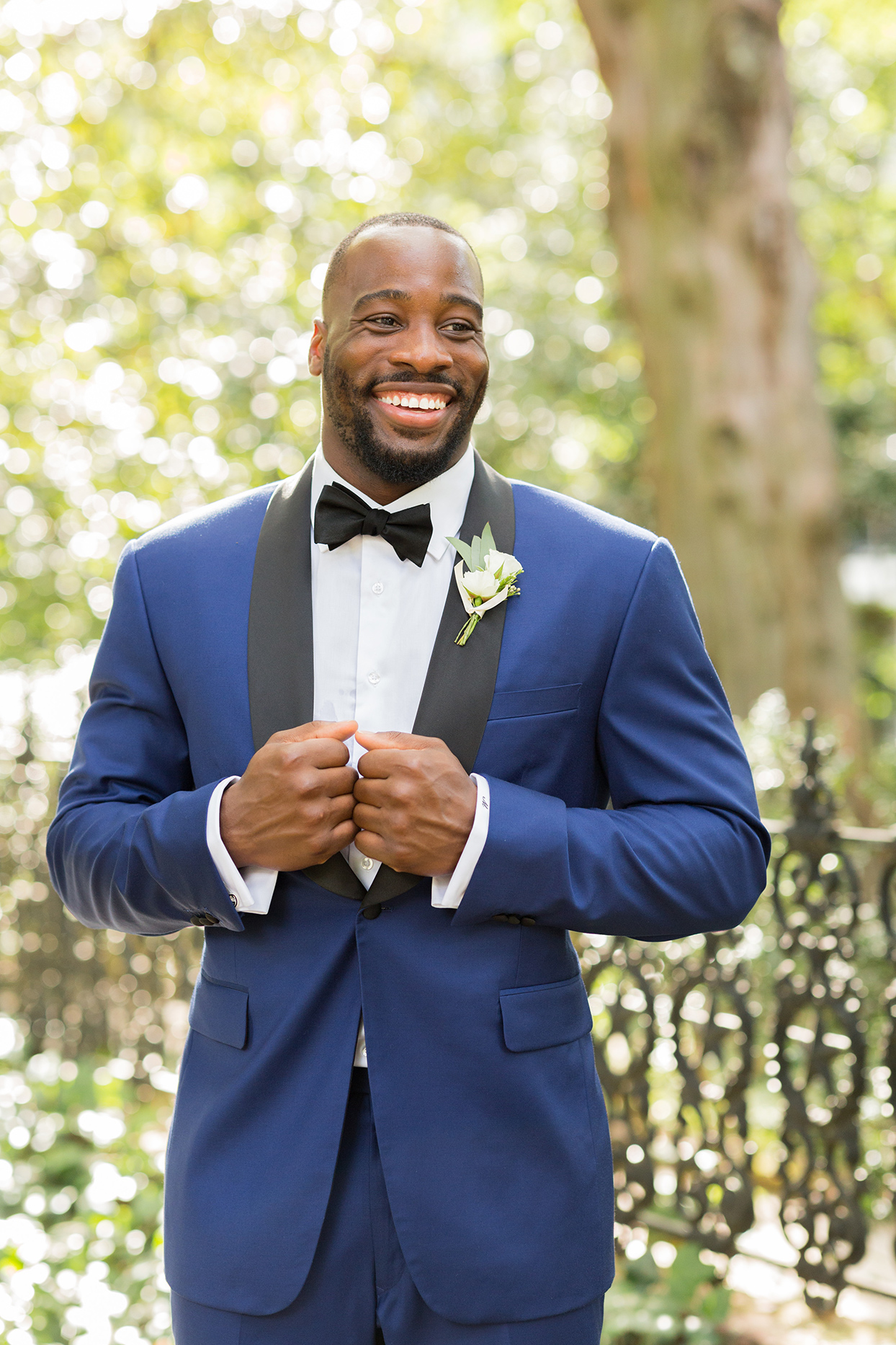 groom smiling wearing navy-blue tuxedo with bowtie