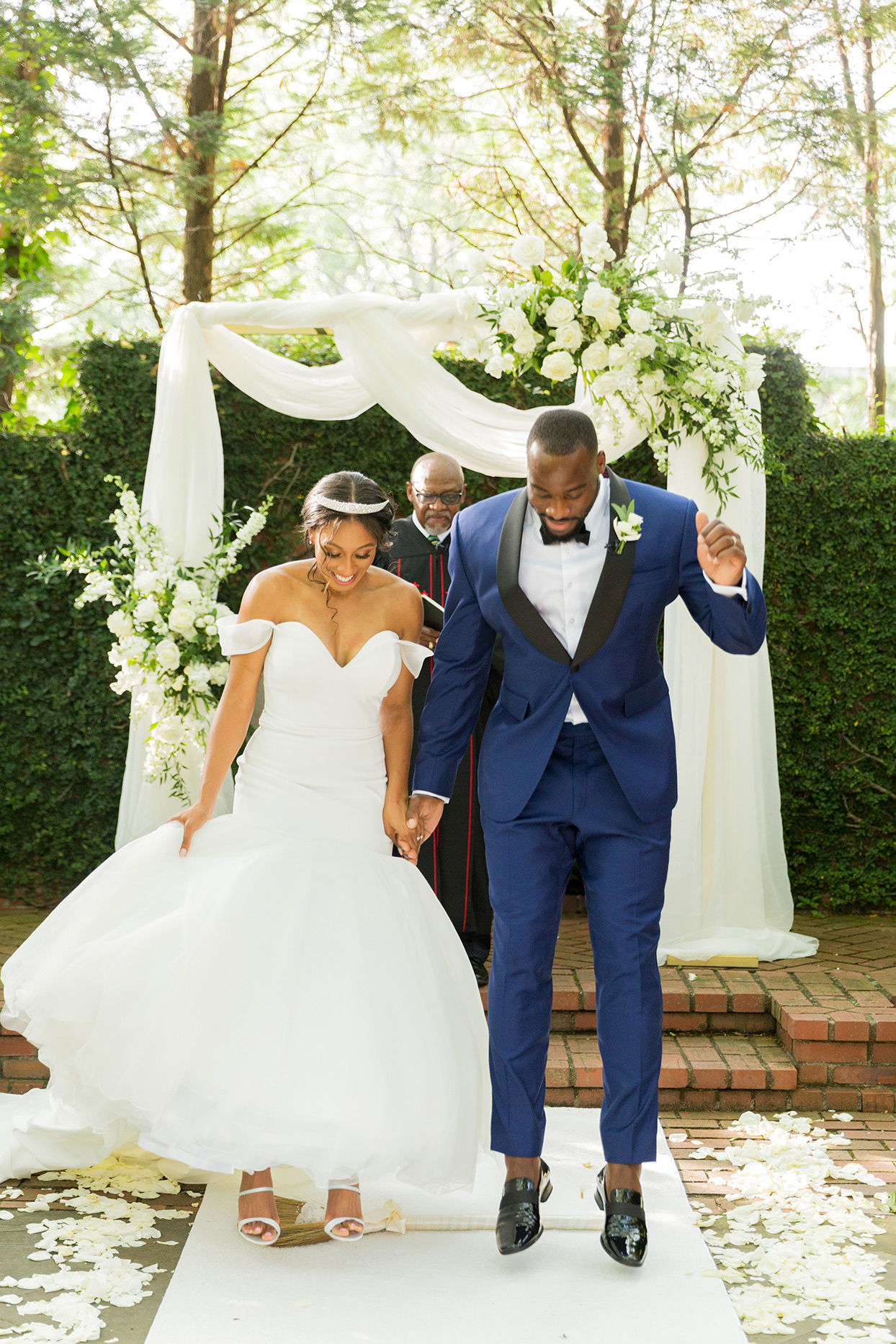 bride and groom holding hands during jumping the broom