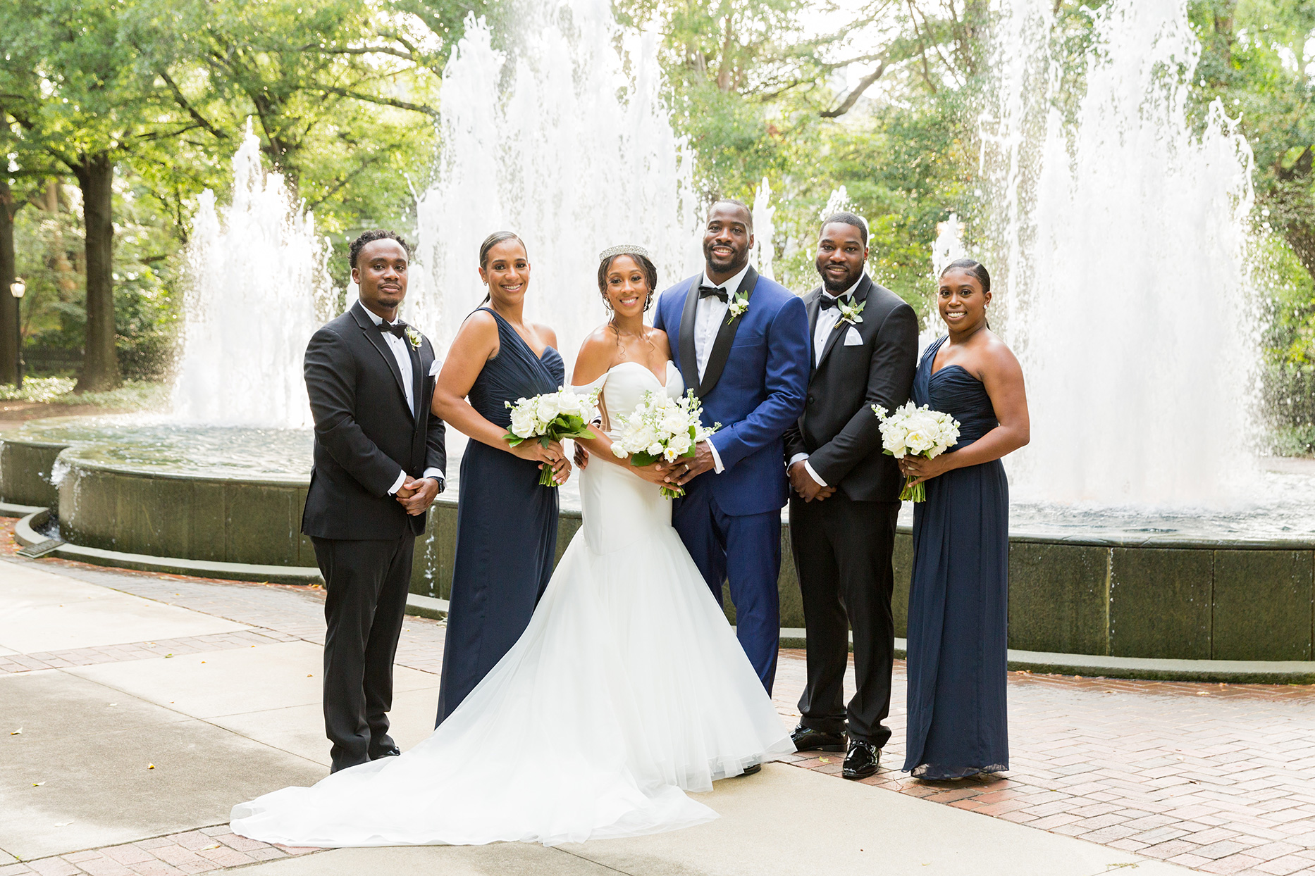 bride and groom smiling with their wedding party attendants