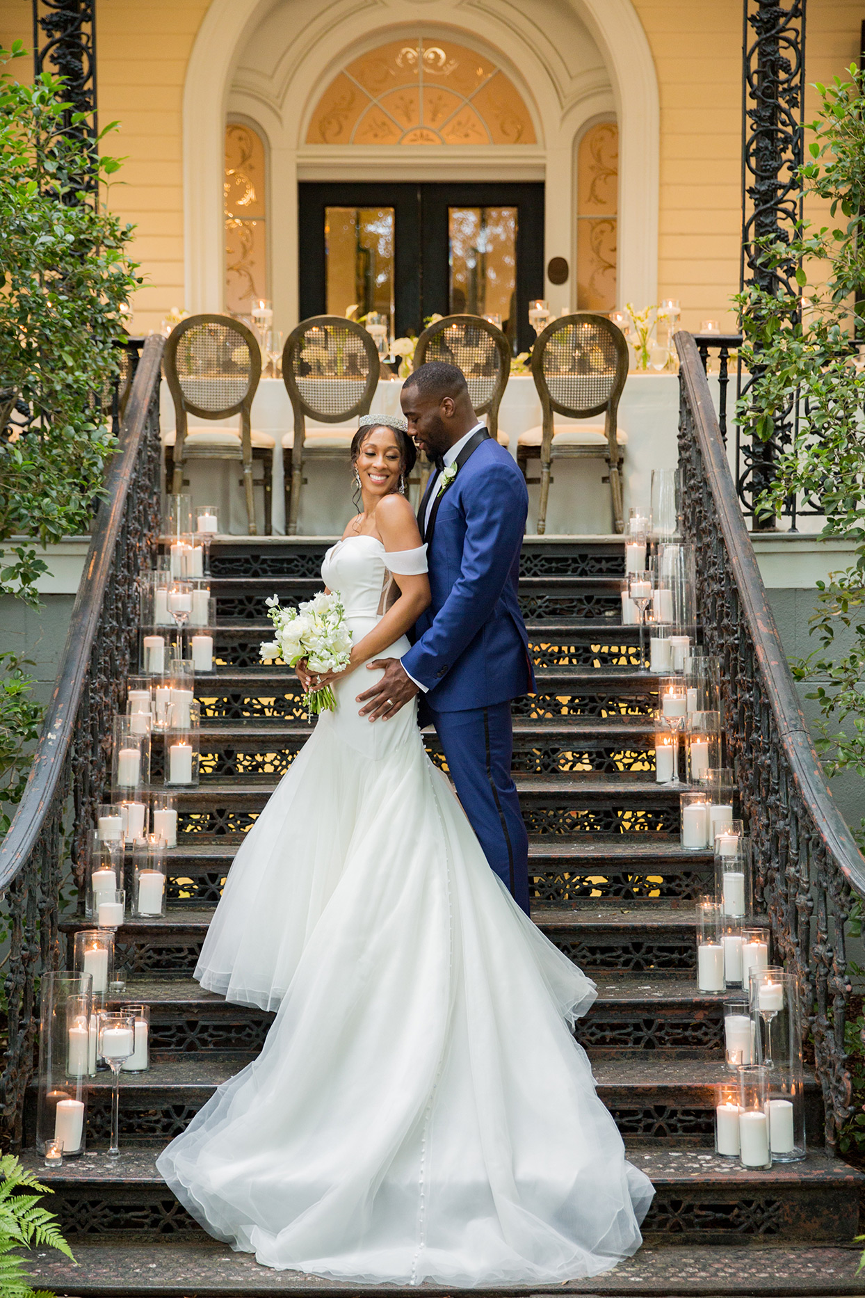 groom standing behind bride on staircase as she looks over her shoulder back at him