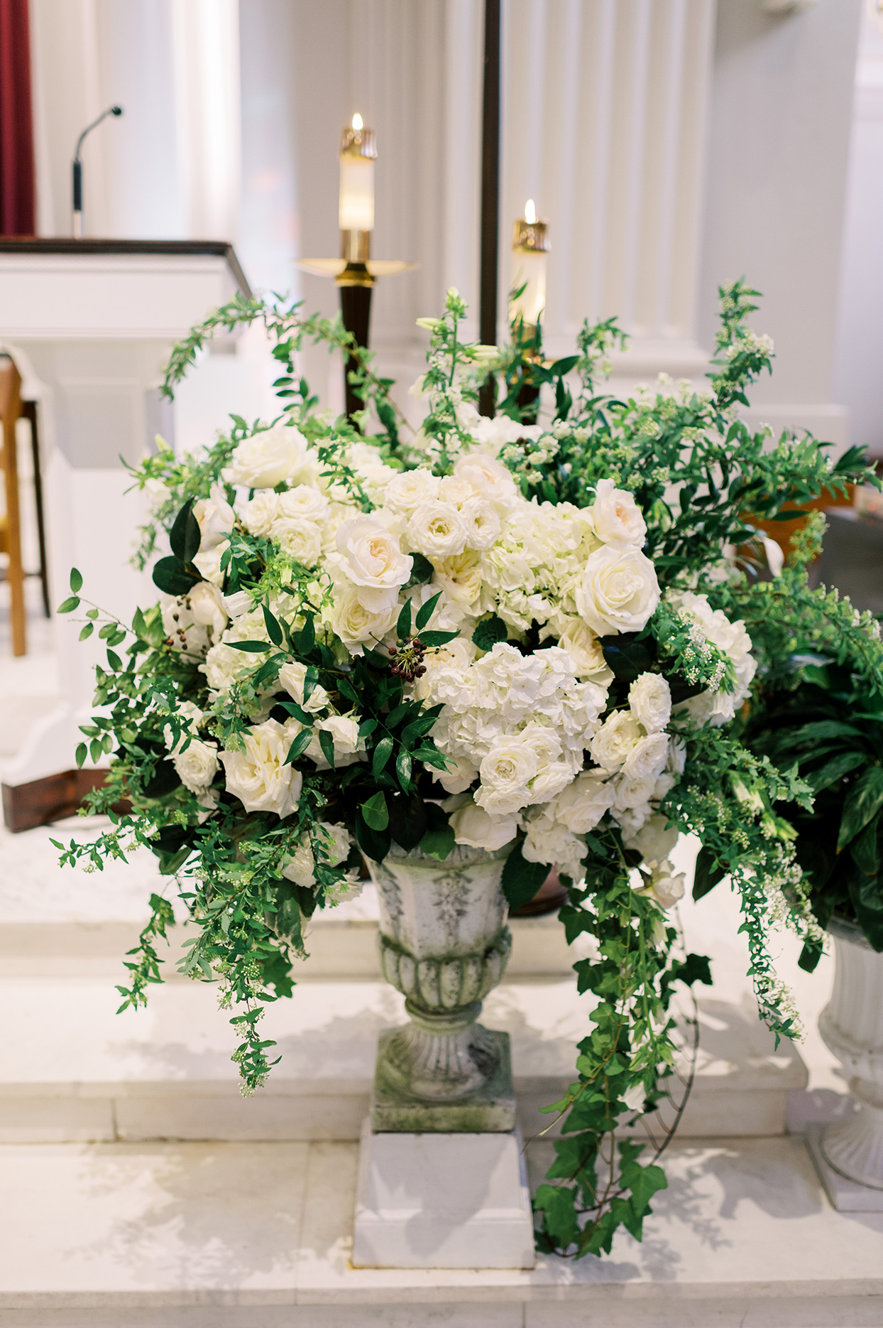 white roses and green vines in classic pots