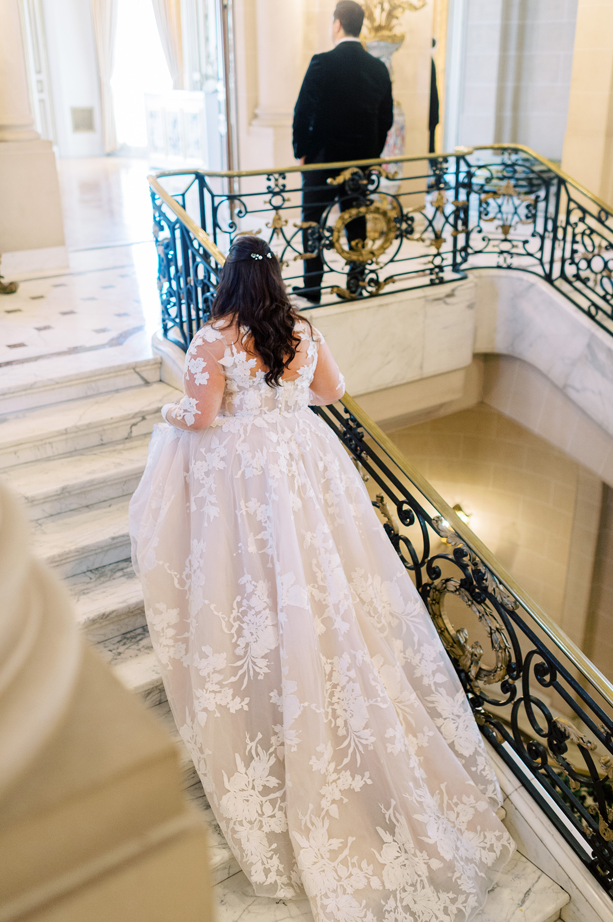 bride walking up stairs to groom for first look