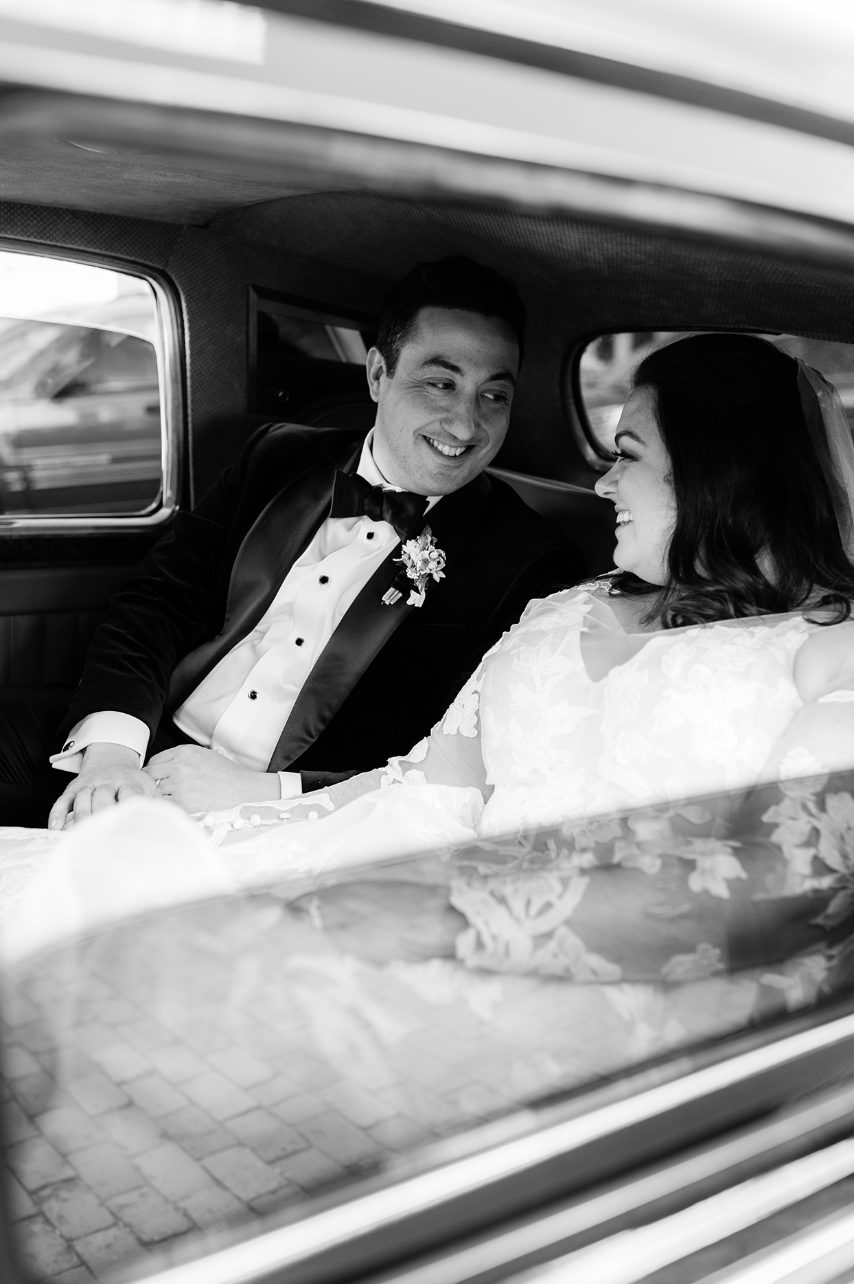 groom and bride smiling at each other in car