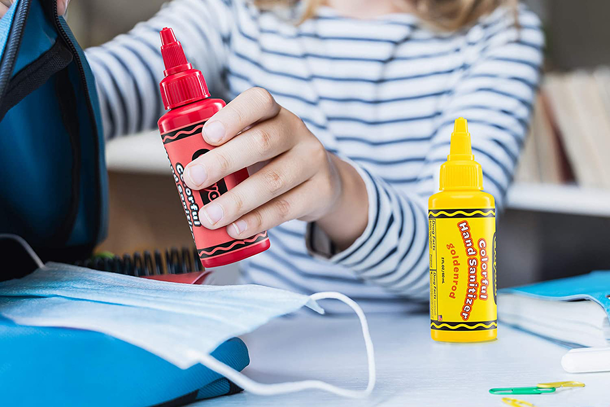 girl putting red Crayola hand sanitizer into backpack