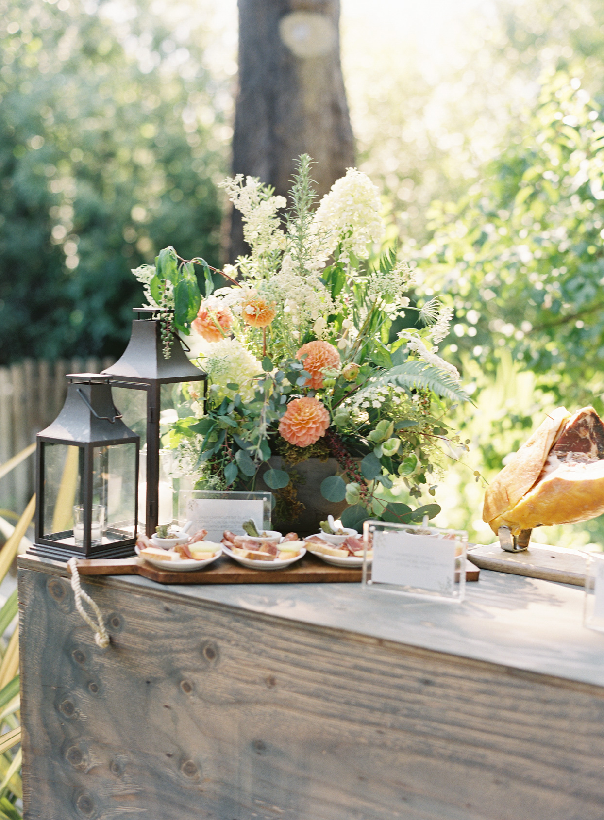 outdoor wooden wedding appetizer station with orange flowers