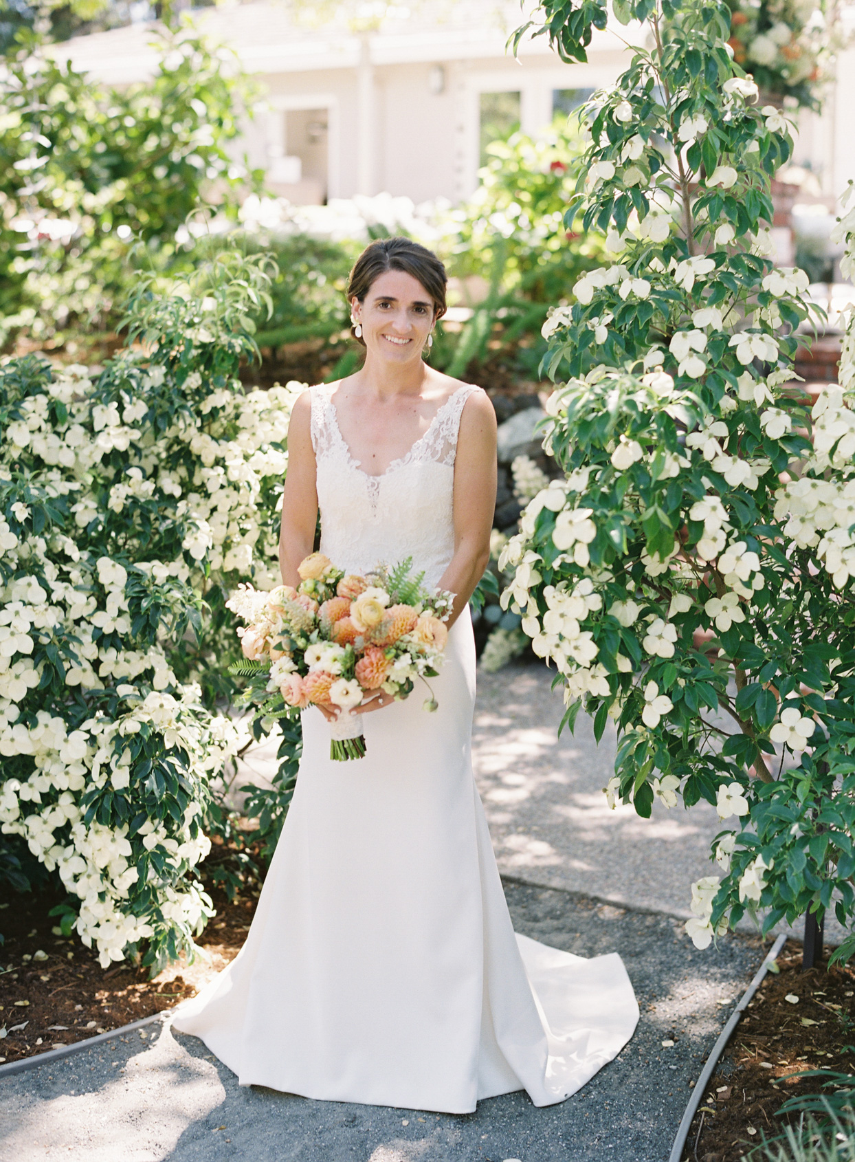 bride standing on path between white floral bushes