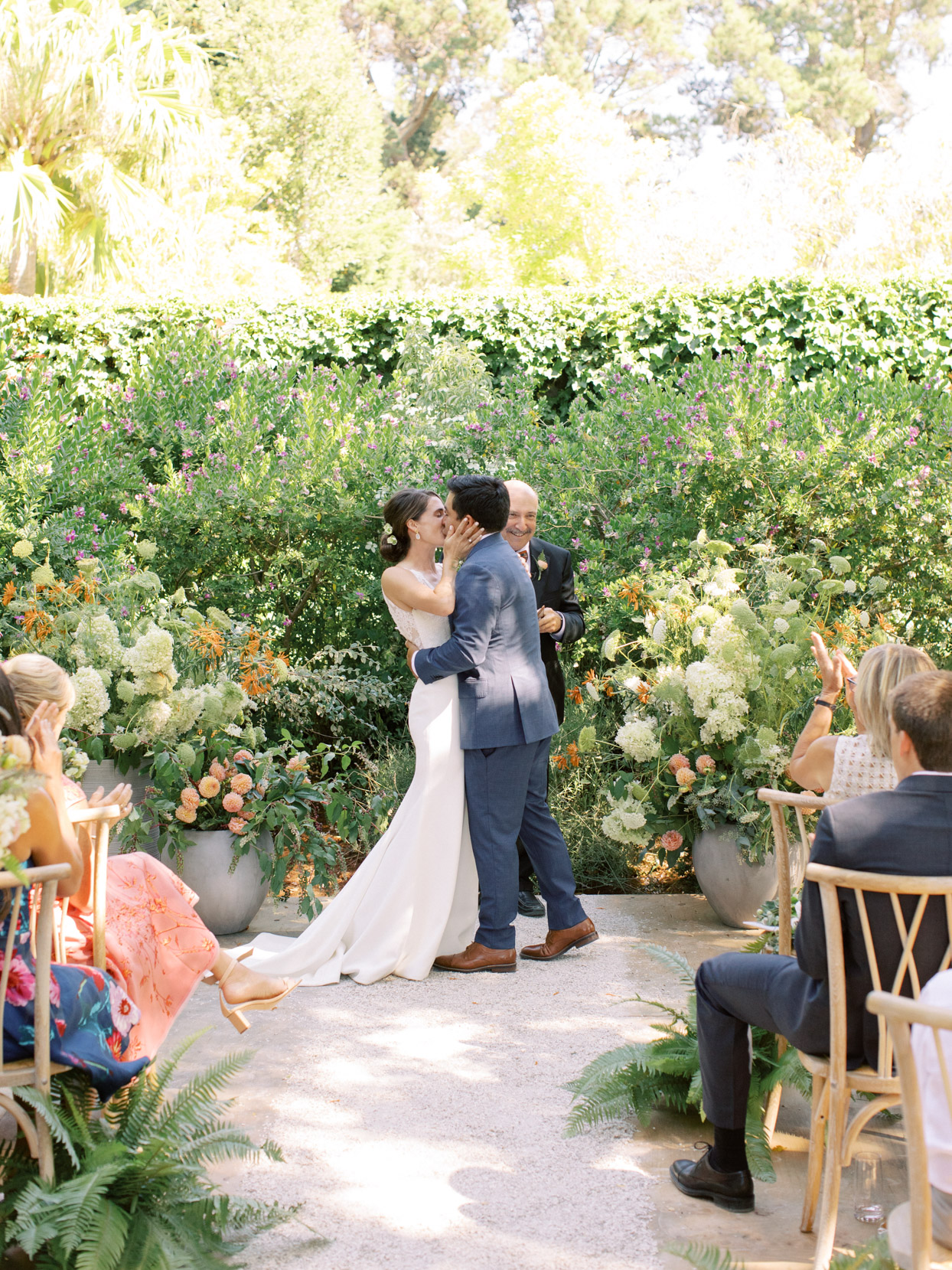 wedding ceremony kiss with floral and greenery backdrop