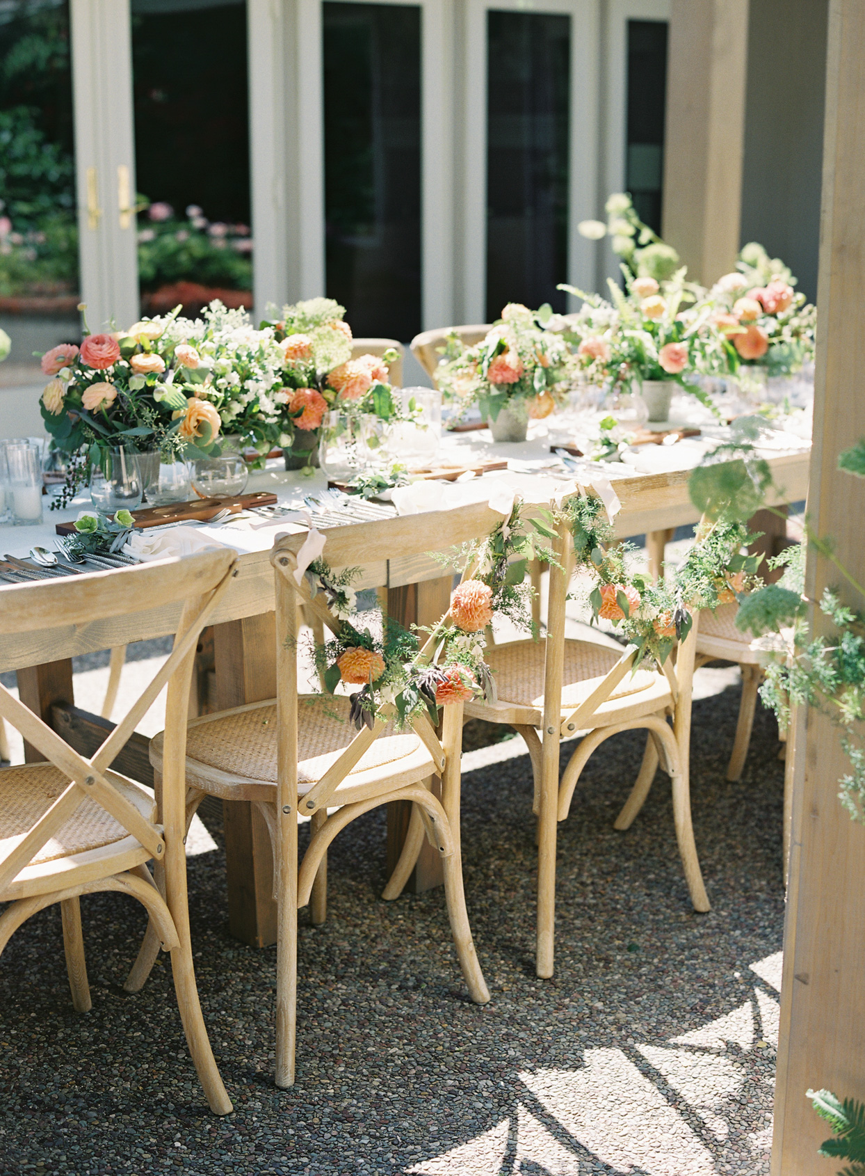 light wood outdoor reception tables with floral garlands