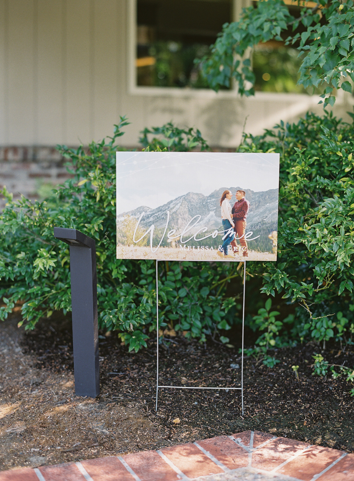 wedding welcome sign against bushes