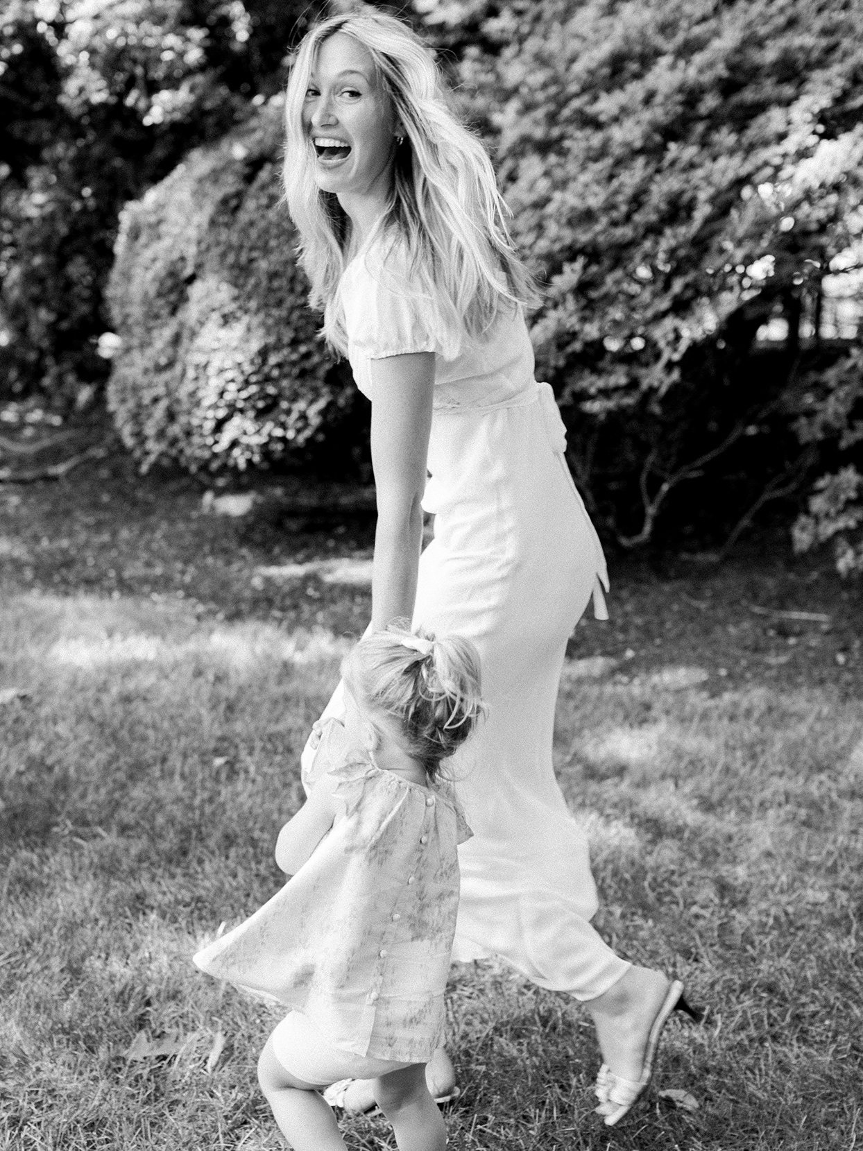 bride holding hand of small child and laughing outside