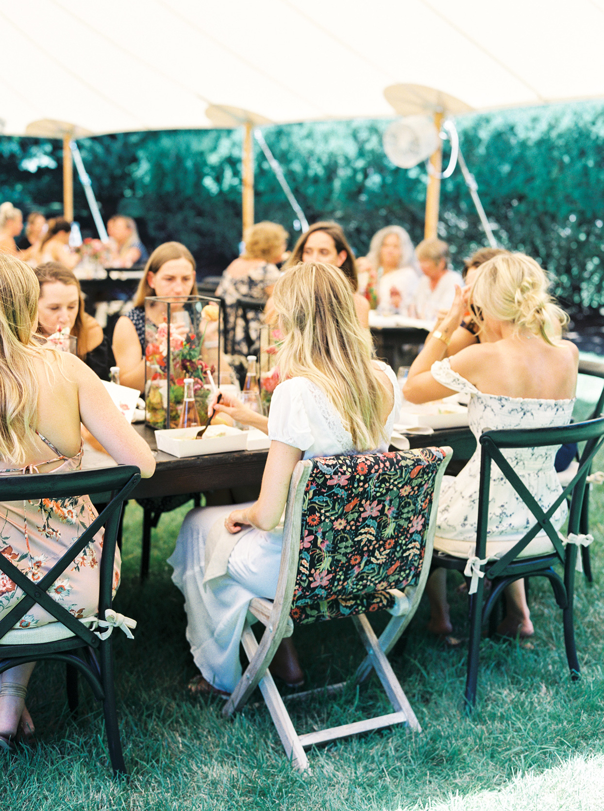 bridal shower guests sitting under white outdoor tent
