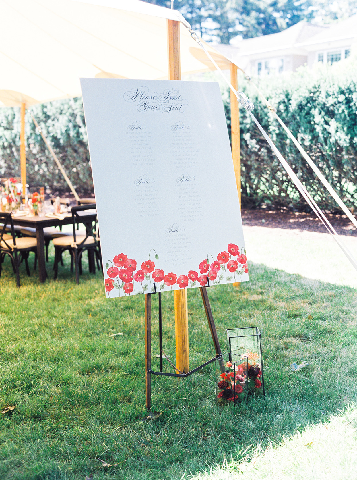 bridal shower seating chart stand next to white tent