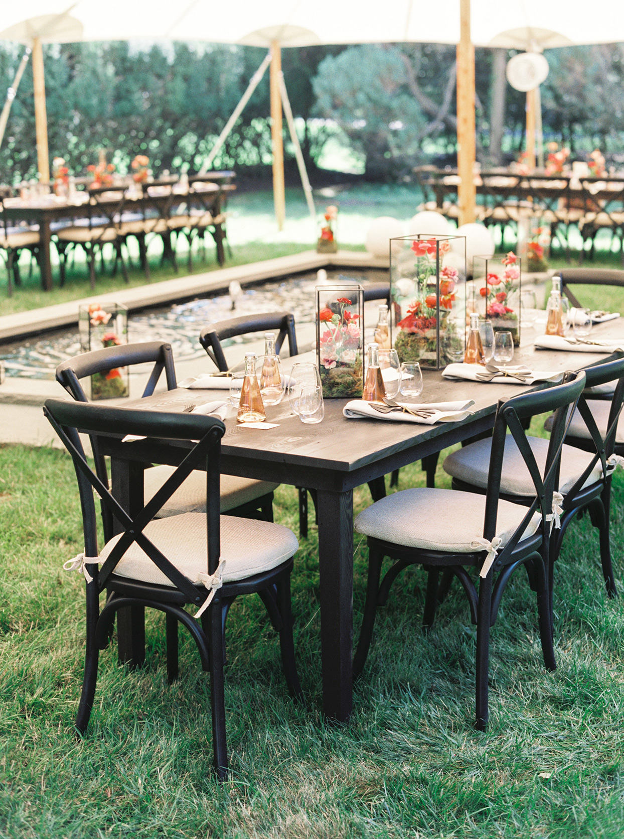 black tables outdoors under white bridal shower tent