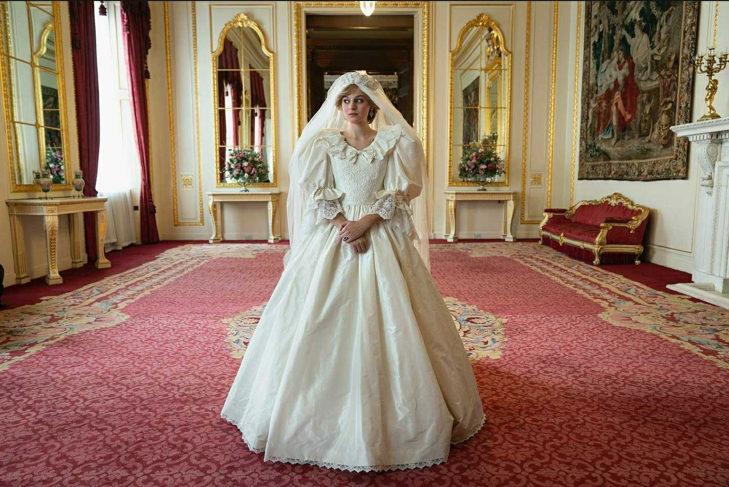 emma corrin on the set of the crown wearing a replica of princess diana's wedding dress