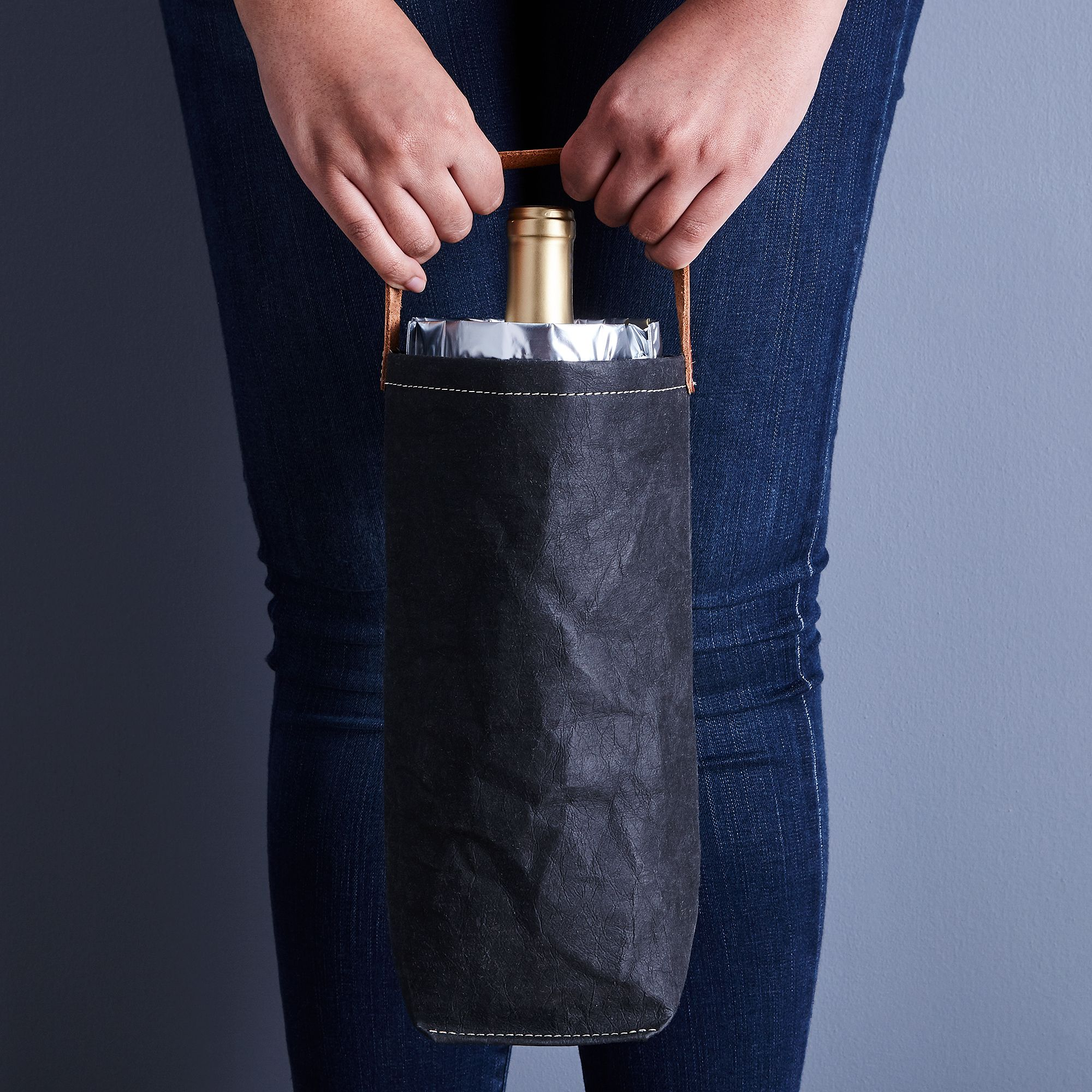 hands holding black canvas wine bag with bottle of wine