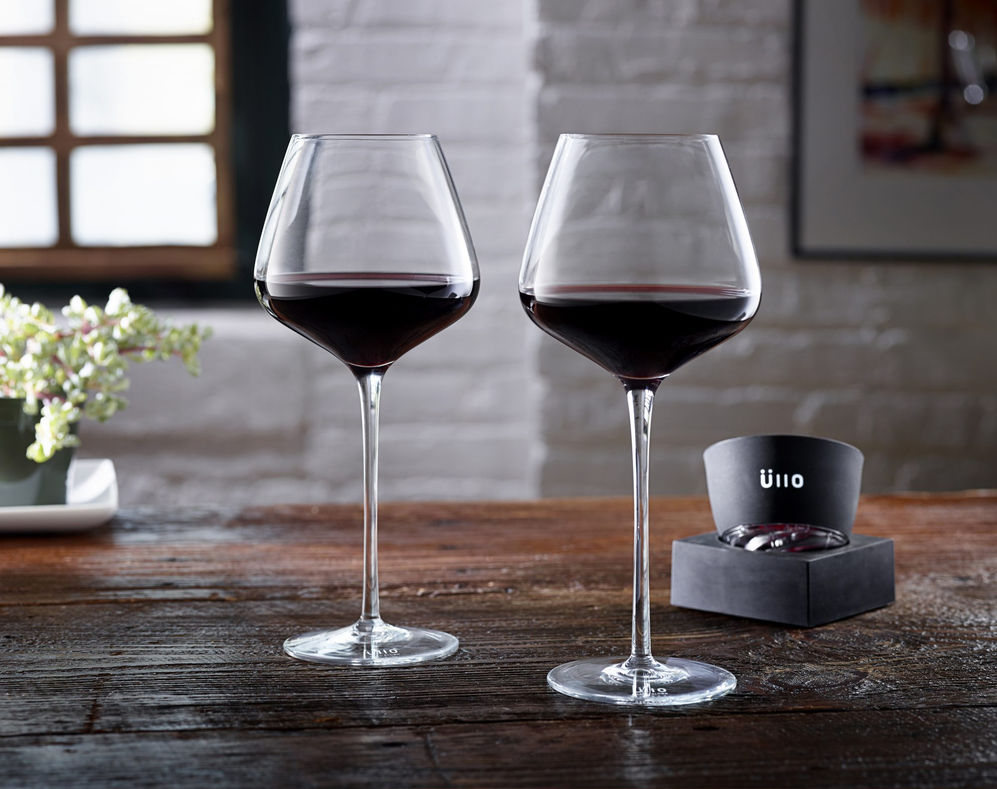 Two glasses of red wine on wooden surface with wine aerator