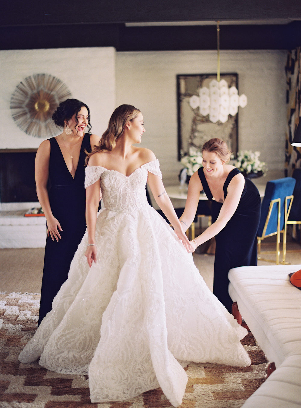 bride putting on off-the-shoulder wedding dress with her bridesmaids' help